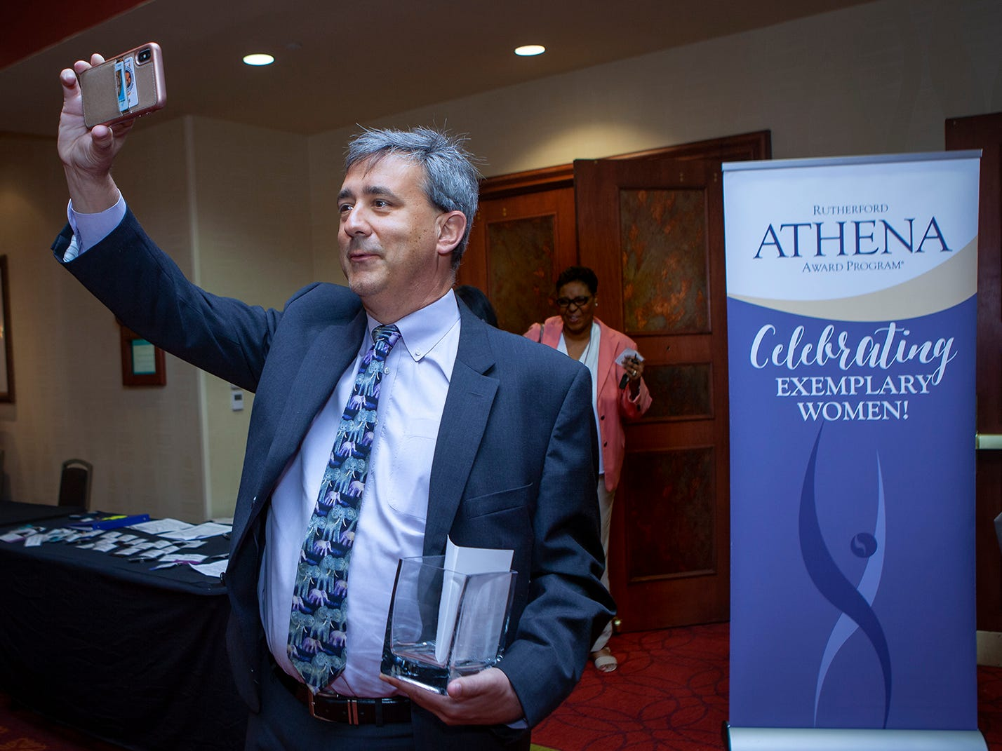Peter Demos takes a photo of his wife Kristin Demos, a nominee for an ATHENA Award, and friends at the celebration hosted by Rutherford Cable Friday, April 12, 2019 at Embassy Suites Murfreesboro.
