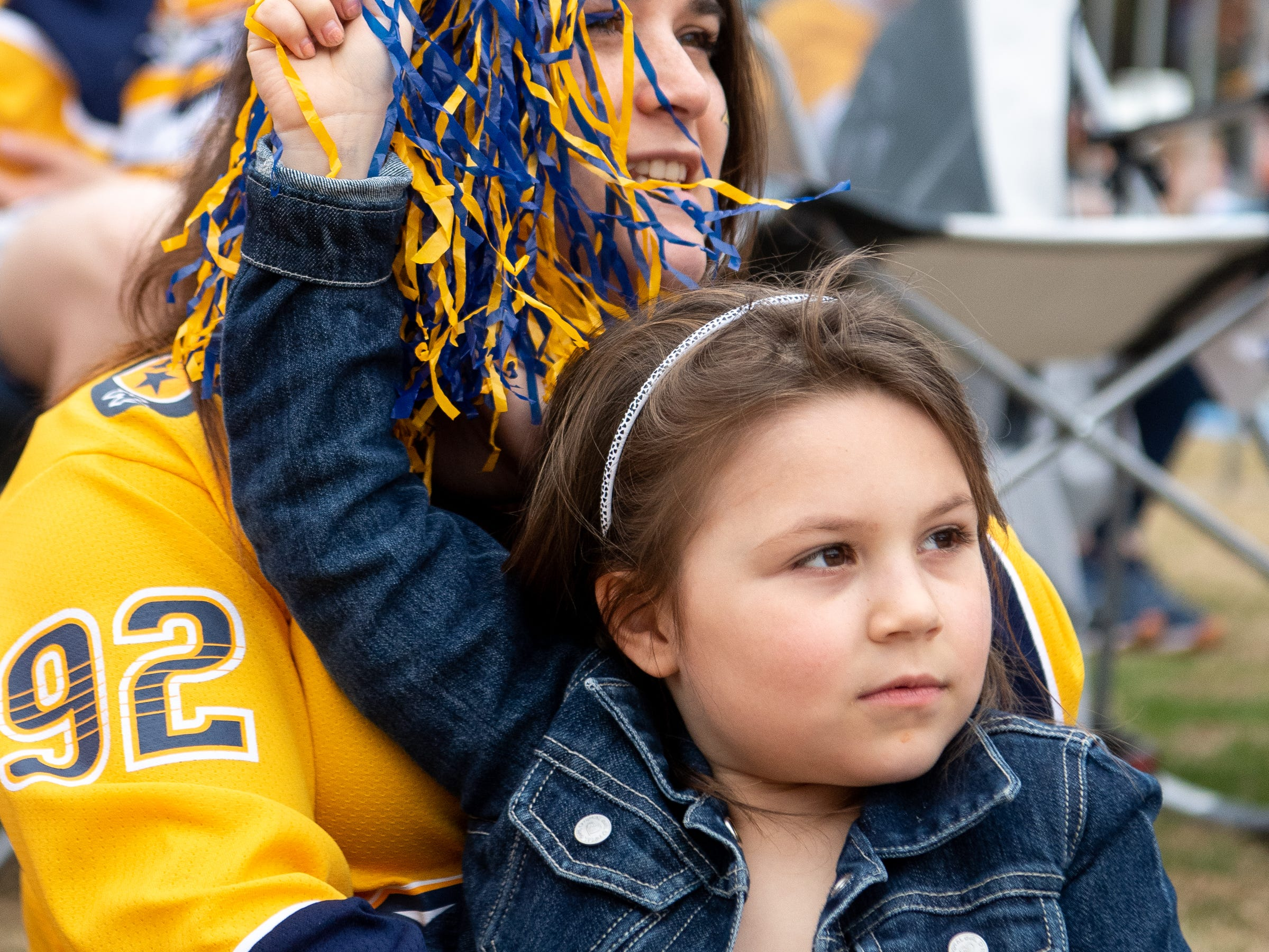 Lily, 6, covers her mom, Chante Bennett's face as she tries to watch the first period during the Nashville Predators game against the Dallas Stars at Preds Party in the Park at Walk of Fame Park Saturday, April 13, 2019, in Nashville, Tenn.
