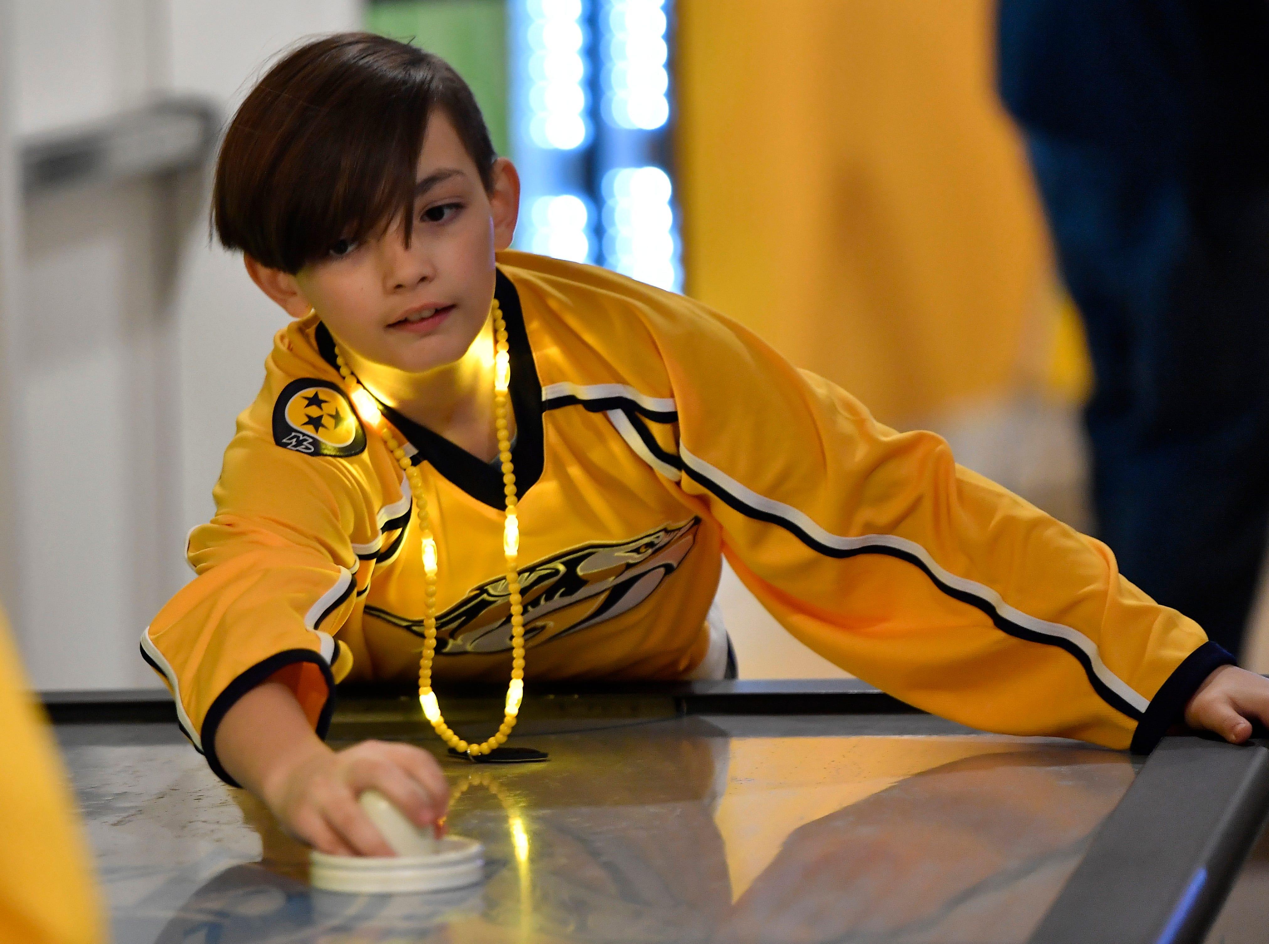 Hayden Brown, 11, plays air hockey before the start of the Predators' divisional semifinal game against Dallas at Bridgestone Arena in Nashville, Tenn., Saturday, April 13, 2019.