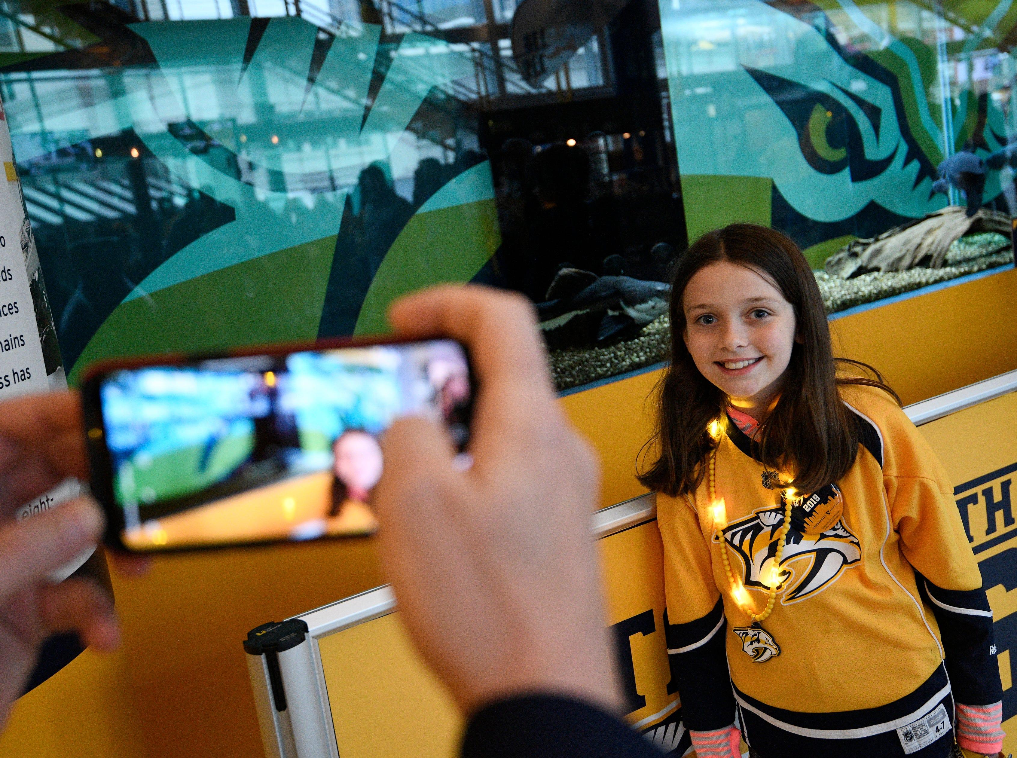 Amelia Scanlan, 9, poses for a photo by the catfish before the Predators' divisional semifinal game against Dallas at Bridgestone Arena in Nashville, Tenn., Saturday, April 13, 2019.
