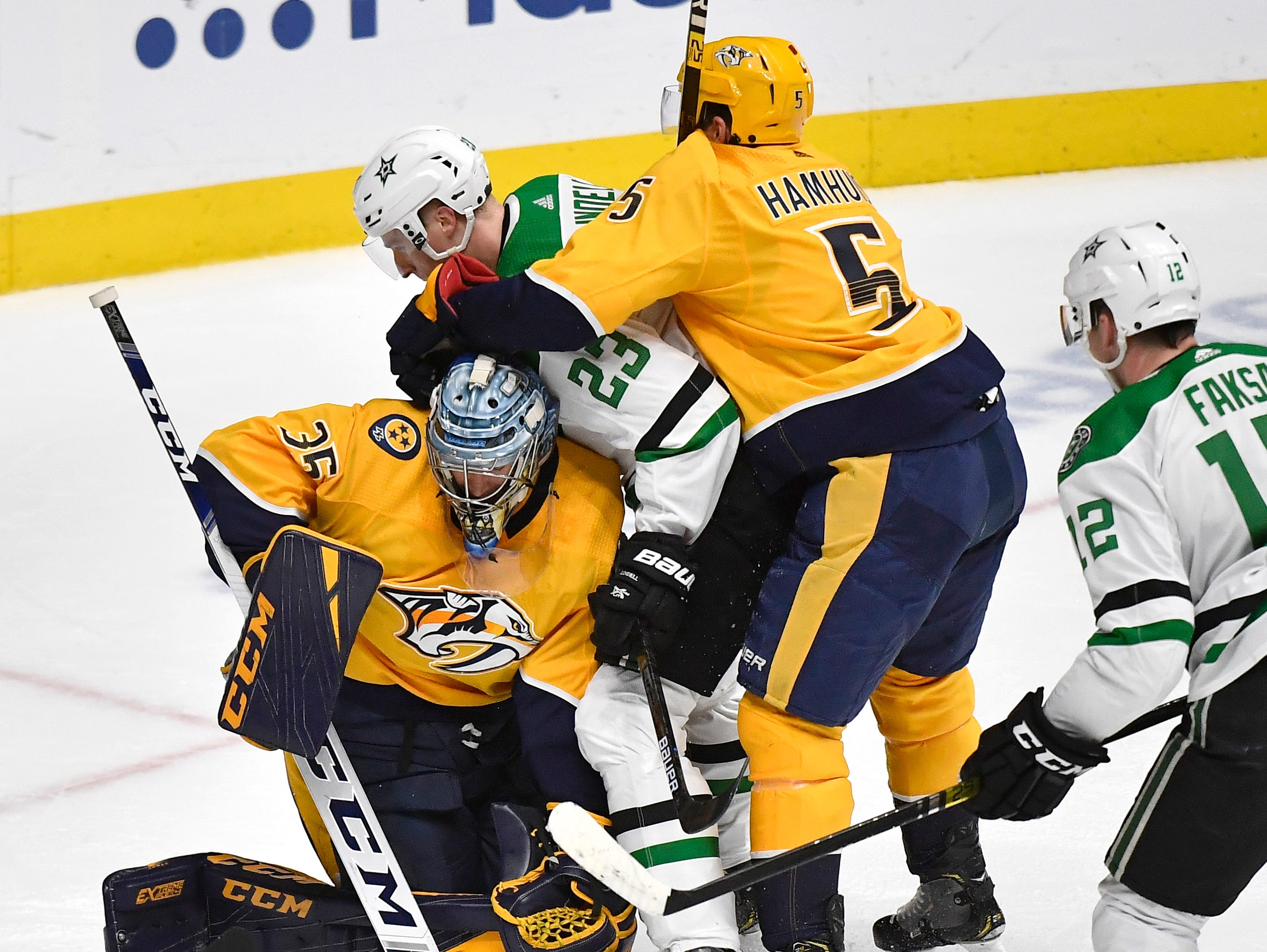 Dallas Stars defenseman Esa Lindell (23) collides with Nashville Predators goaltender Pekka Rinne (35) as Nashville Predators defenseman Dan Hamhuis (5) tries to pull him away during the first period of the divisional semifinal game at Bridgestone Arena in Nashville, Tenn., Saturday, April 13, 2019.