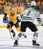 Nashville Predators defenseman Mattias Ekholm (14) moves the puck, defended by Dallas Stars defenseman Miro Heiskanen (4), during the first period Saturday. The Predators won 2-1 in overtime to even the series at 1-1.