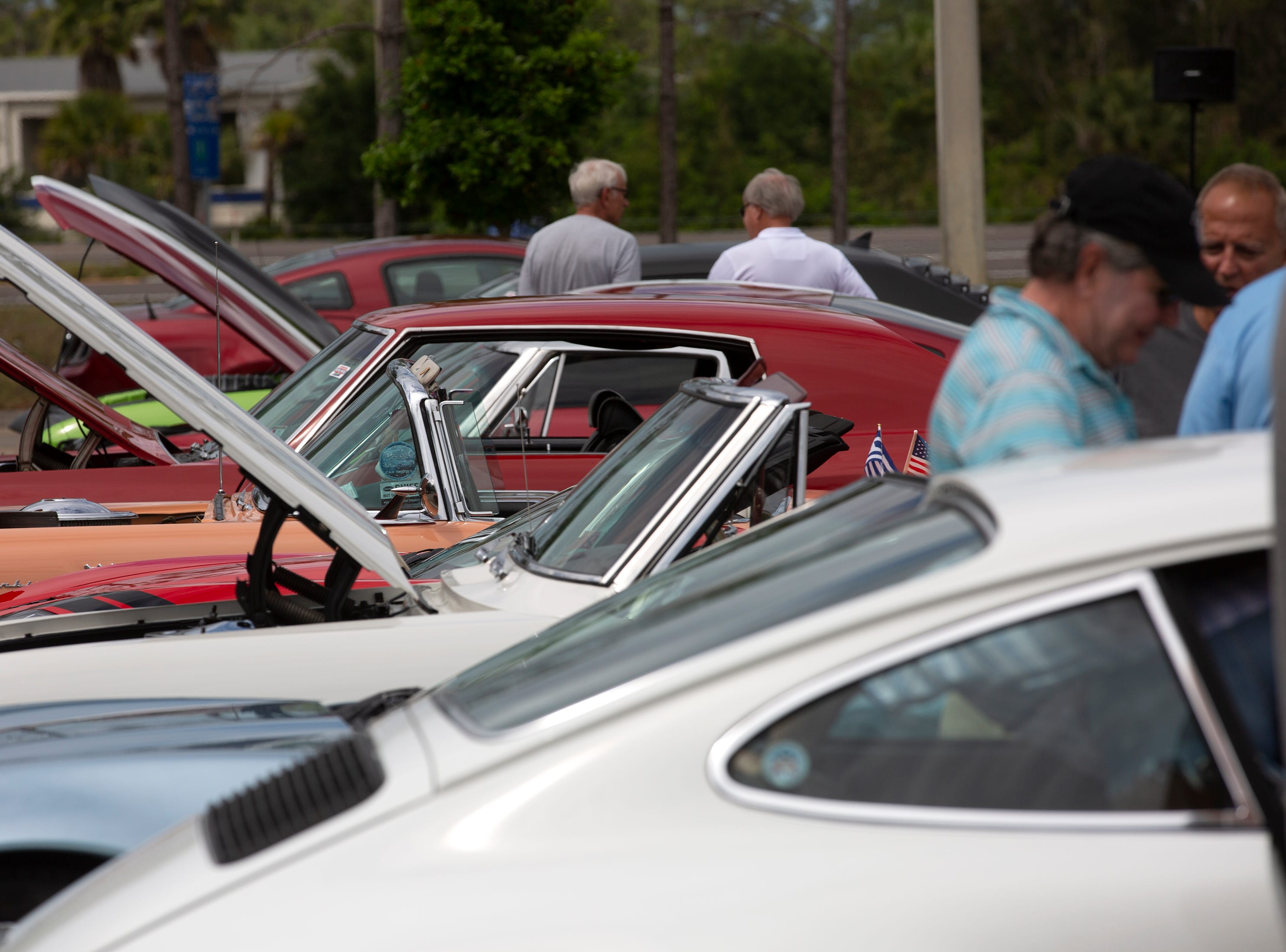 Cars enthusiasts look at cars displayed in a parking lot at the Miromar Outlets during the Cruis'n for a Cause event on Saturday, April 13, 2019 in Estero.