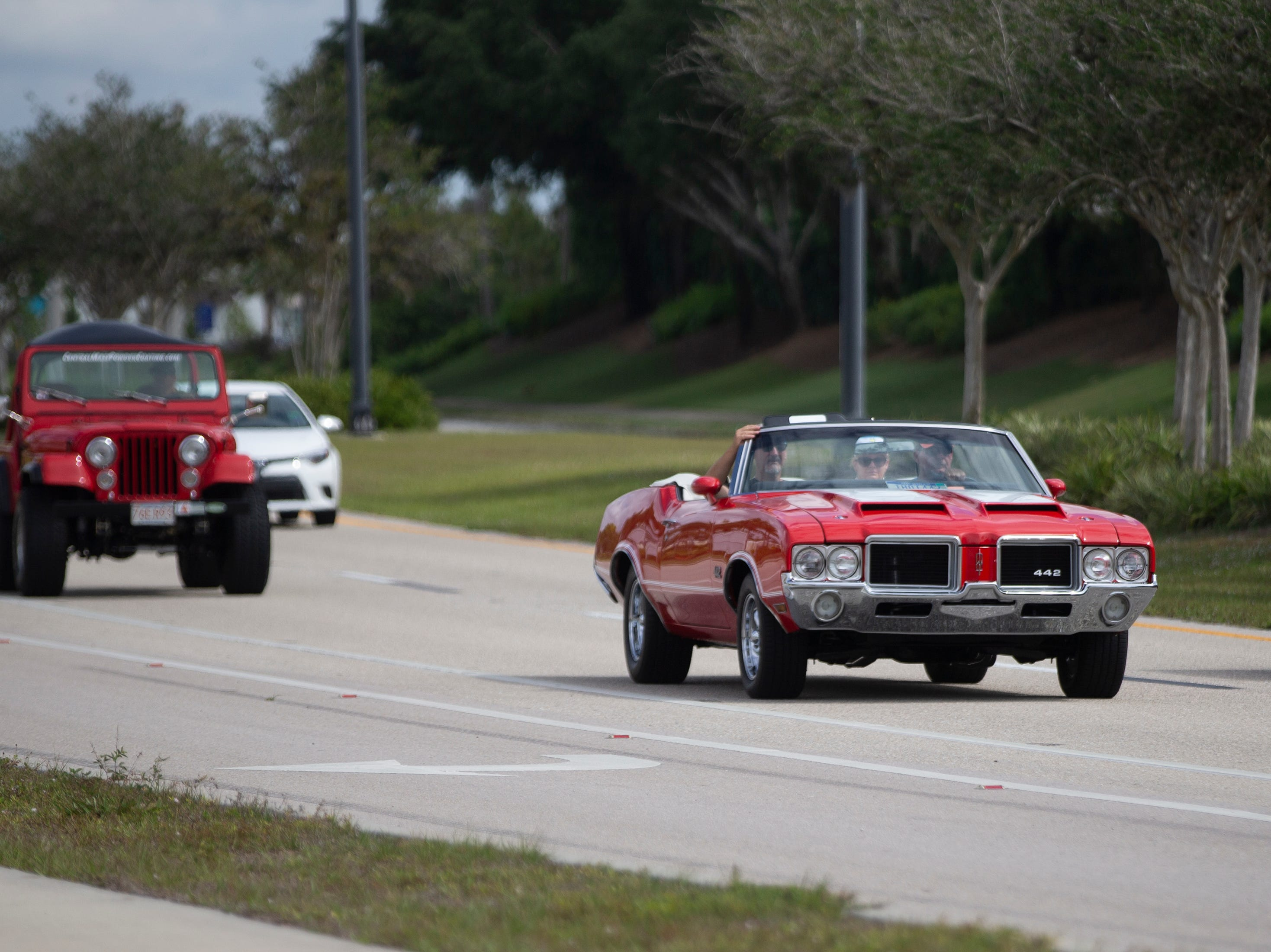Cape Coral residents Paul Perzyk, Ross Smith and Terri Smith ride in Terri's 1971 Oldsmobile 442 during Cruis'n for a Cause event on Saturday, April 13, 2019 in Estero.