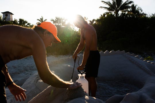 Dan Duling and Daniel Pensenti build a dragon in the sand to accompany the pinwheel garden at the Naples Pier on April 13, 2019.