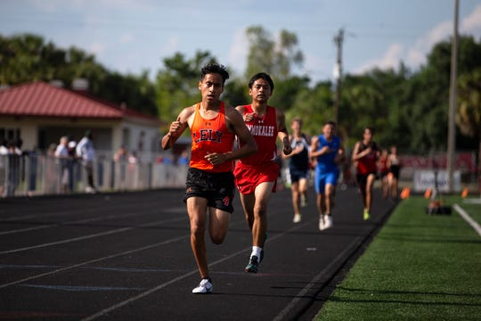 Lely's Ian Rivera Garcia holds a lead in the boys 3200 meter race with Immokalee's Christian Cruz following behind, Friday, April 12, 2019, at Immokalee High School.
