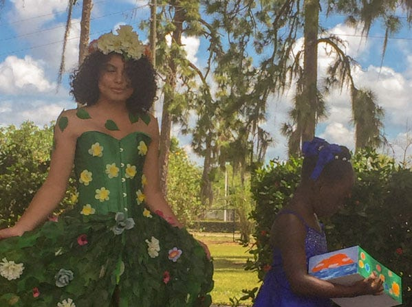 Another recycled fashion dress, locally designed, follows one of the Earth Day art entries in an Immokalee Earth Day procession.