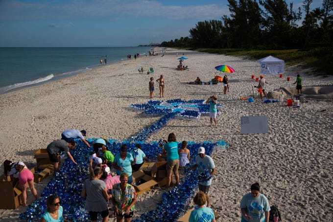 Children's Advocacy Center of Collier County staff, volunteers, and members of the community plant pinwheels in sand at Naples Pier on April 13, 2019. The pinwheel garden was made in an attempt to break the Guinness World Record for the Largest Toy Pinwheel Display in the World and contained 4,435 pinwheels.