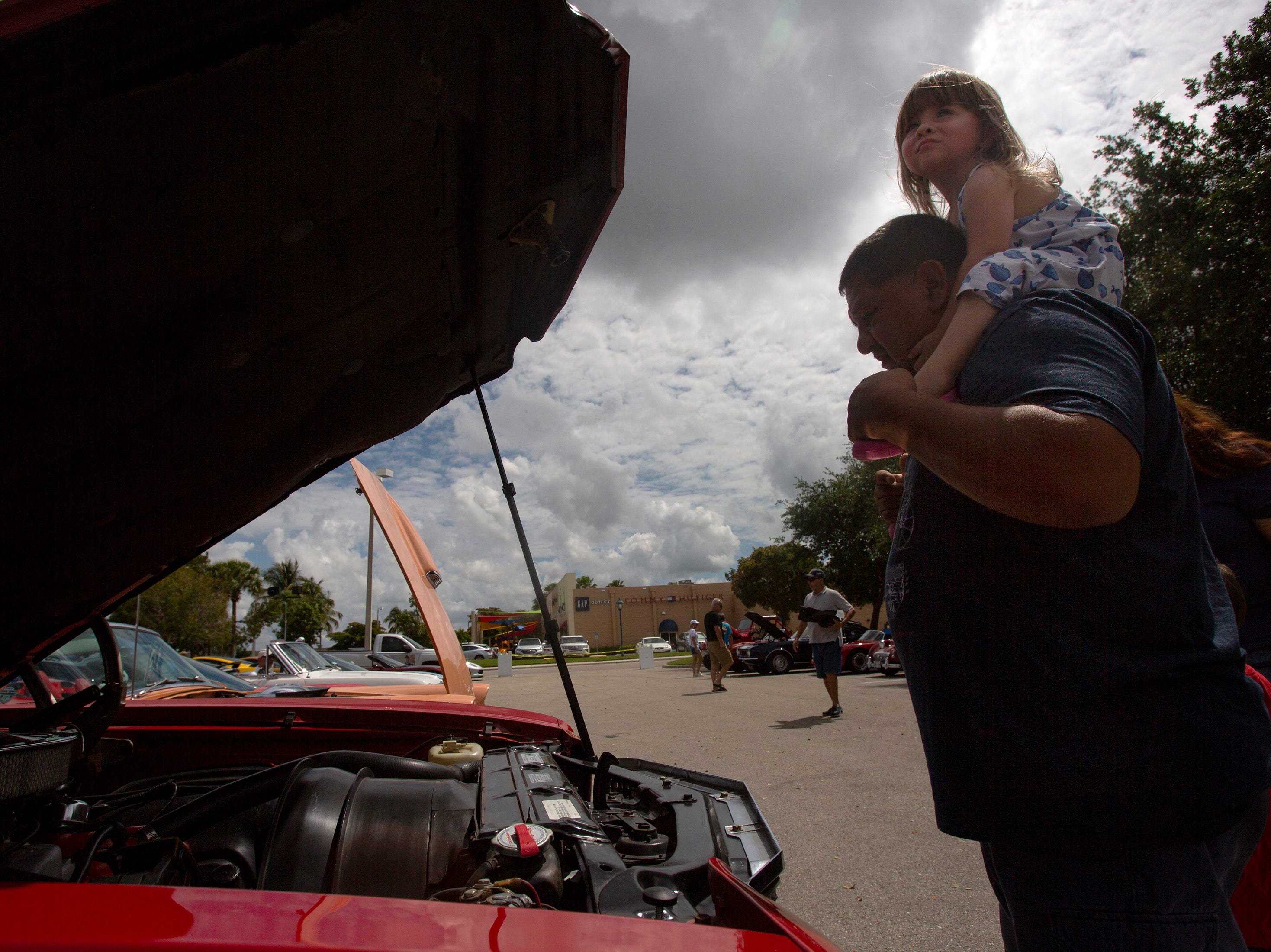 Adolfo Lopez and his friend's daughter Rosalie Abrams both from Estero admire cars together during the Cruis'n for a Cause event on Saturday, April 13, 2019 at the Miromar Outlets in Estero.
