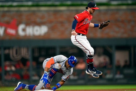 Apr 12, 2019; Atlanta, GA, USA; New York Mets center fielder Keon Broxton (23) slides under Atlanta Braves shortstop Dansby Swanson (7) during the fourth inning at SunTrust Park.