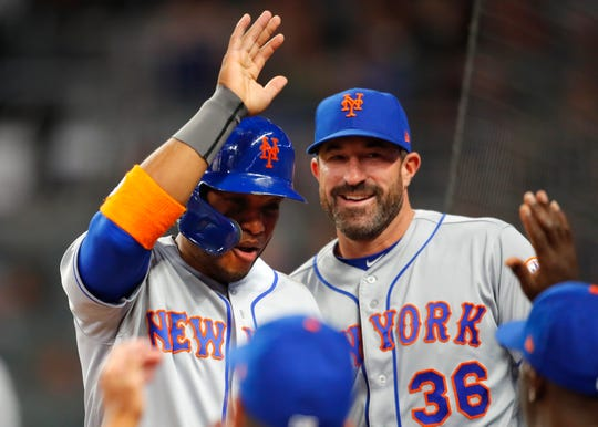 Robinson Cano of the New York Mets celebrates scoring with manager Mickey Callaway in the fourth inning of an MLB game against theAtlanta Braves at SunTrust Park on April 12, 2018 in Atlanta, Georgia.