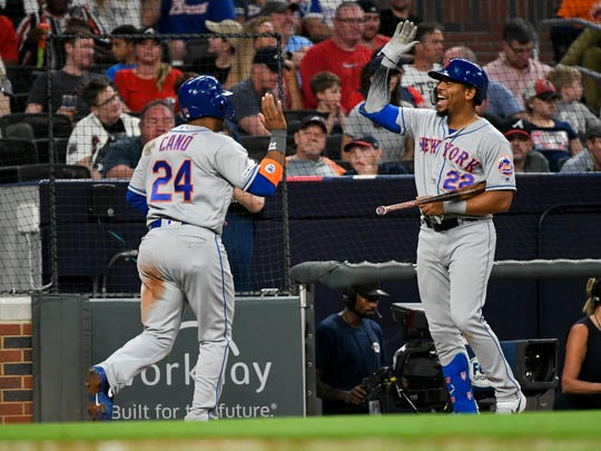 New York Mets Dominic Smith (22) celebrates as Robinson Cano comes to the dugout after scoring on a Michael Conforto double to right field during the fourth inning of a baseball game against the Atlanta Braves, Friday, April 12, 2019, in Atlanta.