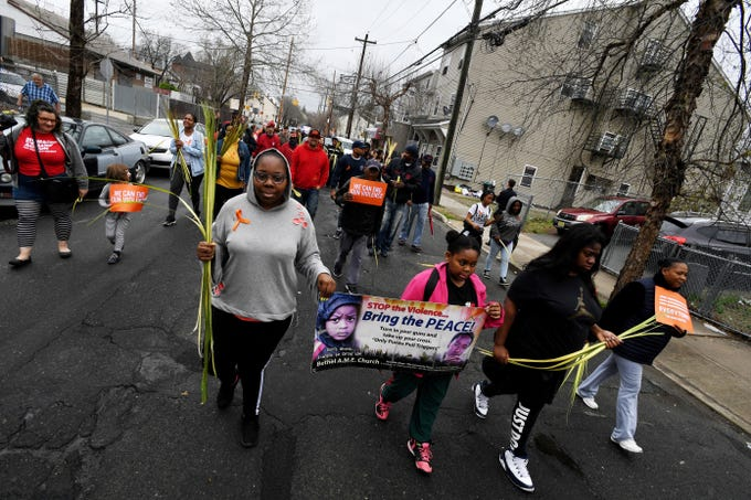 (center) Angela McKinnon and her daughter Nalaisha Clark, 10, hold a sign as they take part in the Paterson Peace March on North Main Street on Saturday, April 13, 2019.