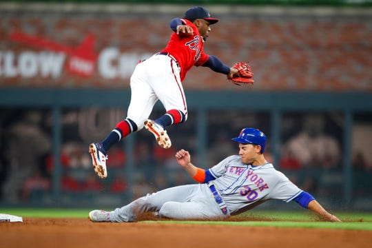 Michael Conforto #30 of the New York Mets slides under Ozzie Albies #1 of the Atlanta Braves for a stolen base in the third inning of an MLB game at SunTrust Park on April 12, 2019 in Atlanta, Georgia.