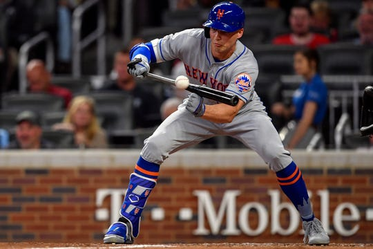 Apr 12, 2019; Atlanta, GA, USA; New York Mets left fielder Brandon Nimmo (9) bunts for a single against the Atlanta Braves during the fourth inning at SunTrust Park.