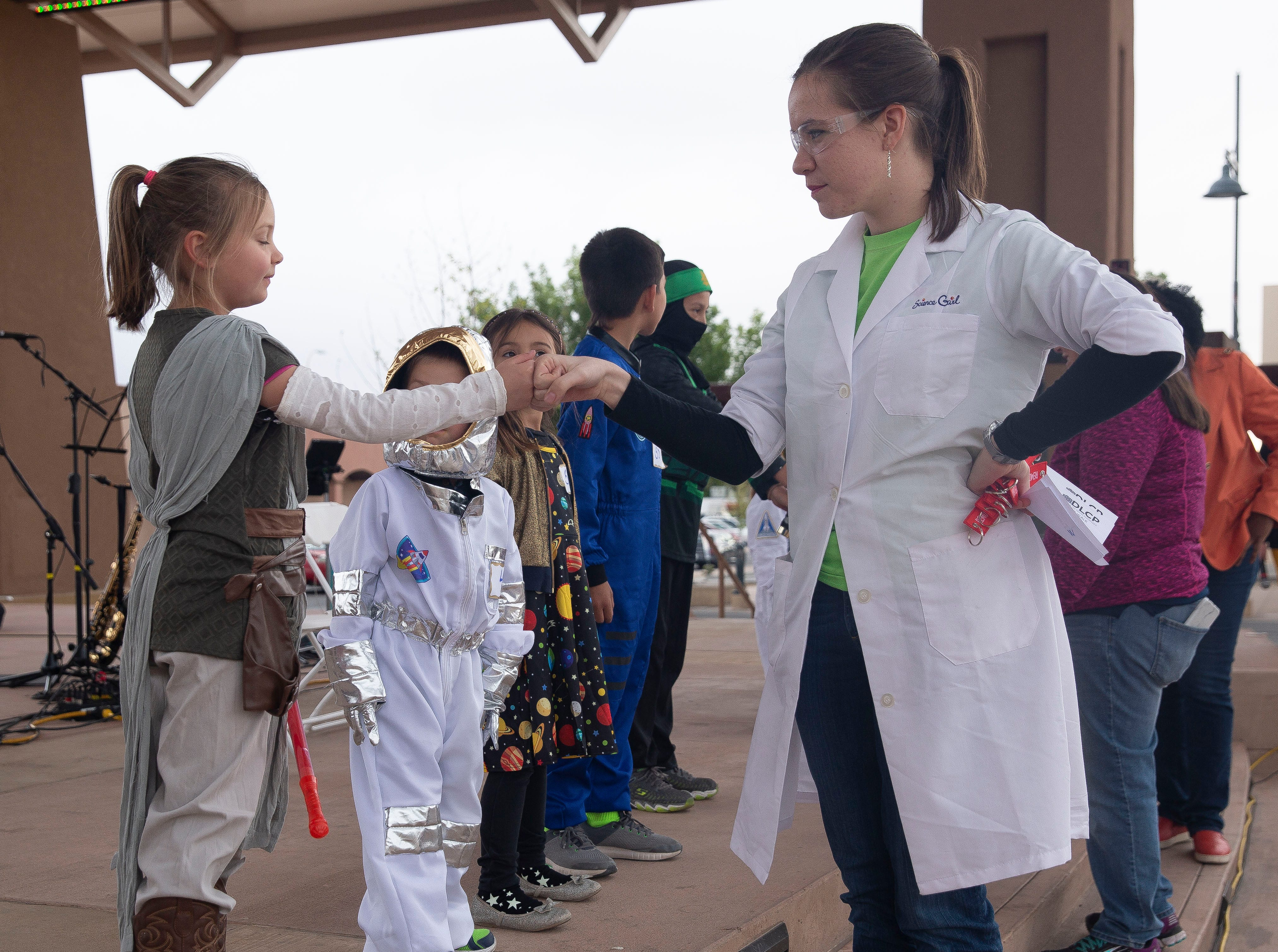 "Science Girl fist bumps ""Rey,"" Liliana Carruth, 7, Friday April 12, 2019, during the Space Walk in downtown Las Cruces."