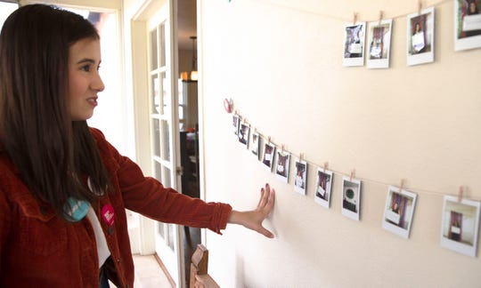 "Las Cruces teen Abrianna Morales, who spearheads the Sexual Assault Youth Support Network, looks at photos taken during an ""I am"" day of empowerment April 14, 2019, in Las Cruces."