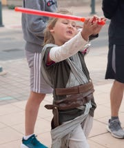 """Dressed as the Star War character """"Rey,"""" Liliana Carruth, 7, swings her light saber Friday April 12, 2019, during the Space Walk in downtown Las Cruces."""