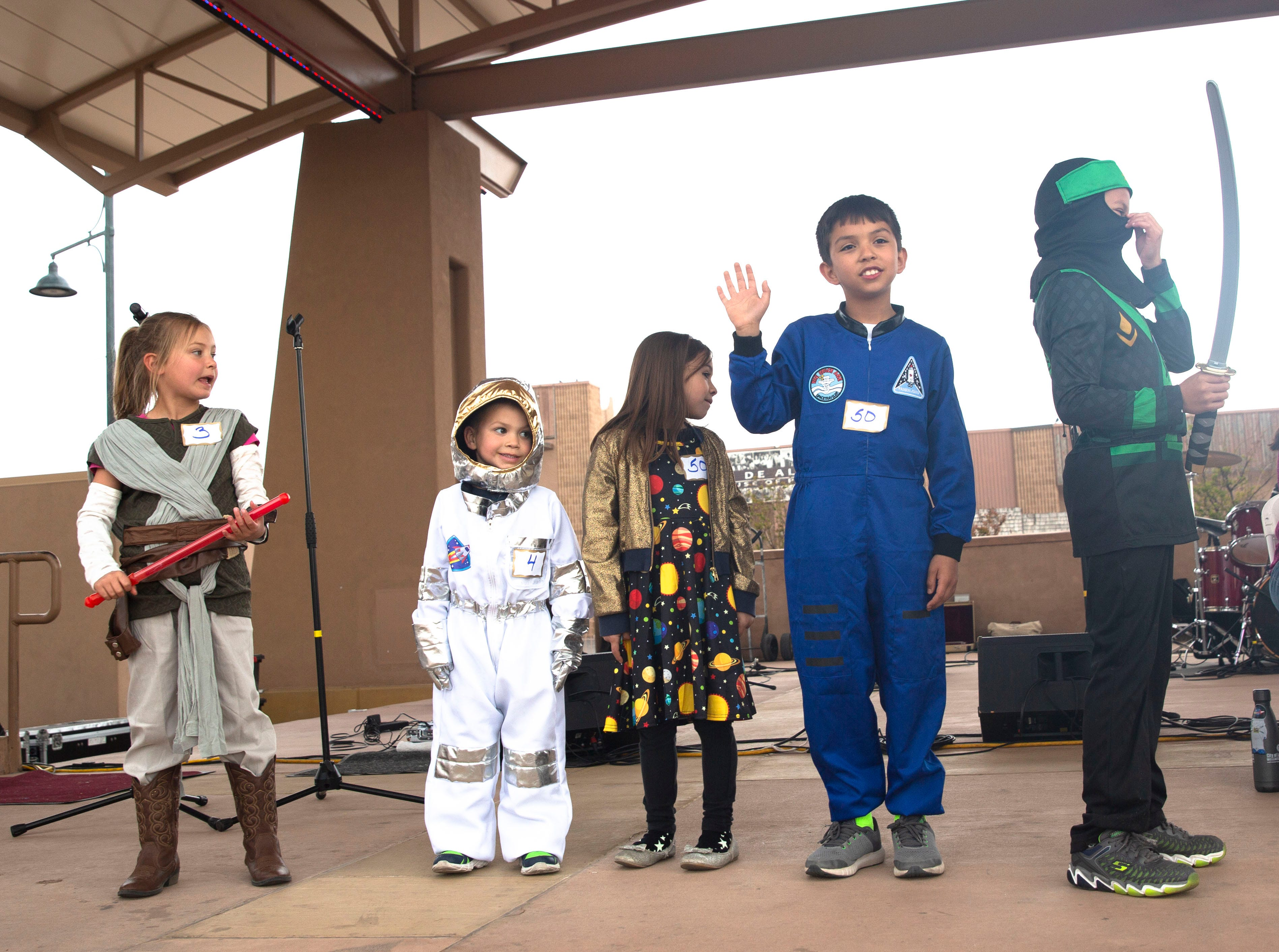 Led by a fierce space ninja, kids line up Friday April 12, 2019, to have their costumes judged during the Space Walk in downtown Las Cruces.
