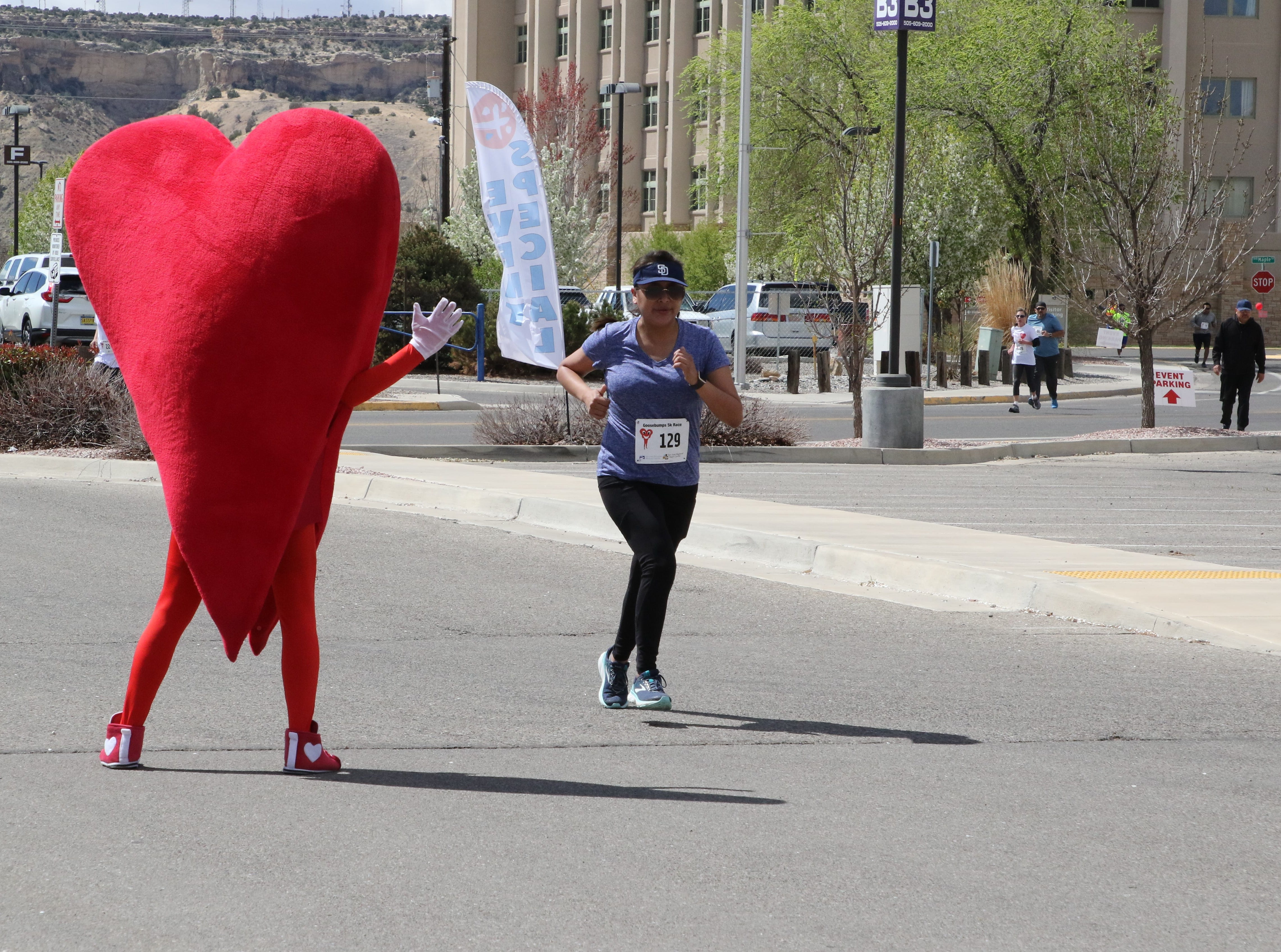 A runner passes Mr. Juan Hart, the San Juan Regional Heart Center's mascot, during the 11th annual A Fair of the Heart and Goosebump Race on Saturday in Farmington.