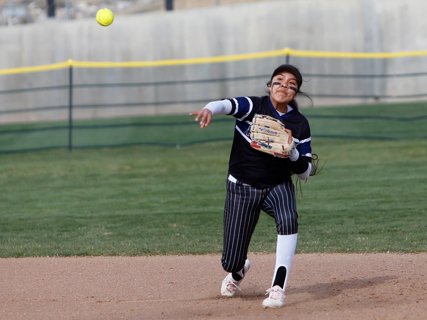 Piedra Vista's Lanae Billy makes a tough throw to first base for an out against Farmington during Friday's District 2-5A game at Farmington Sports Complex.