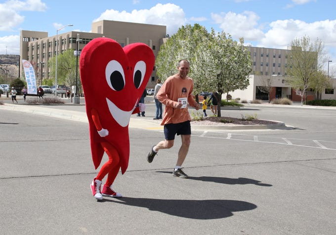 Mr. Juan Hart, the San Juan Regional Heart Center's mascot, encourages a participant to finish the 5K race for the 11th annual A Fair of the Heart and Goosebump Race on Saturday in Farmington.