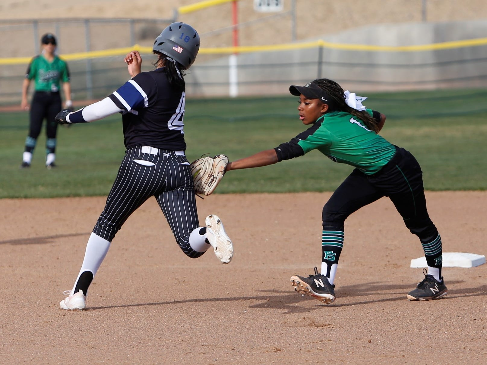 Farmington's Zo Plamer tags out Piedra Vista's Chaunelle Penn in front of second base during Friday's District 2-5A game at Farmington Sports Complex.