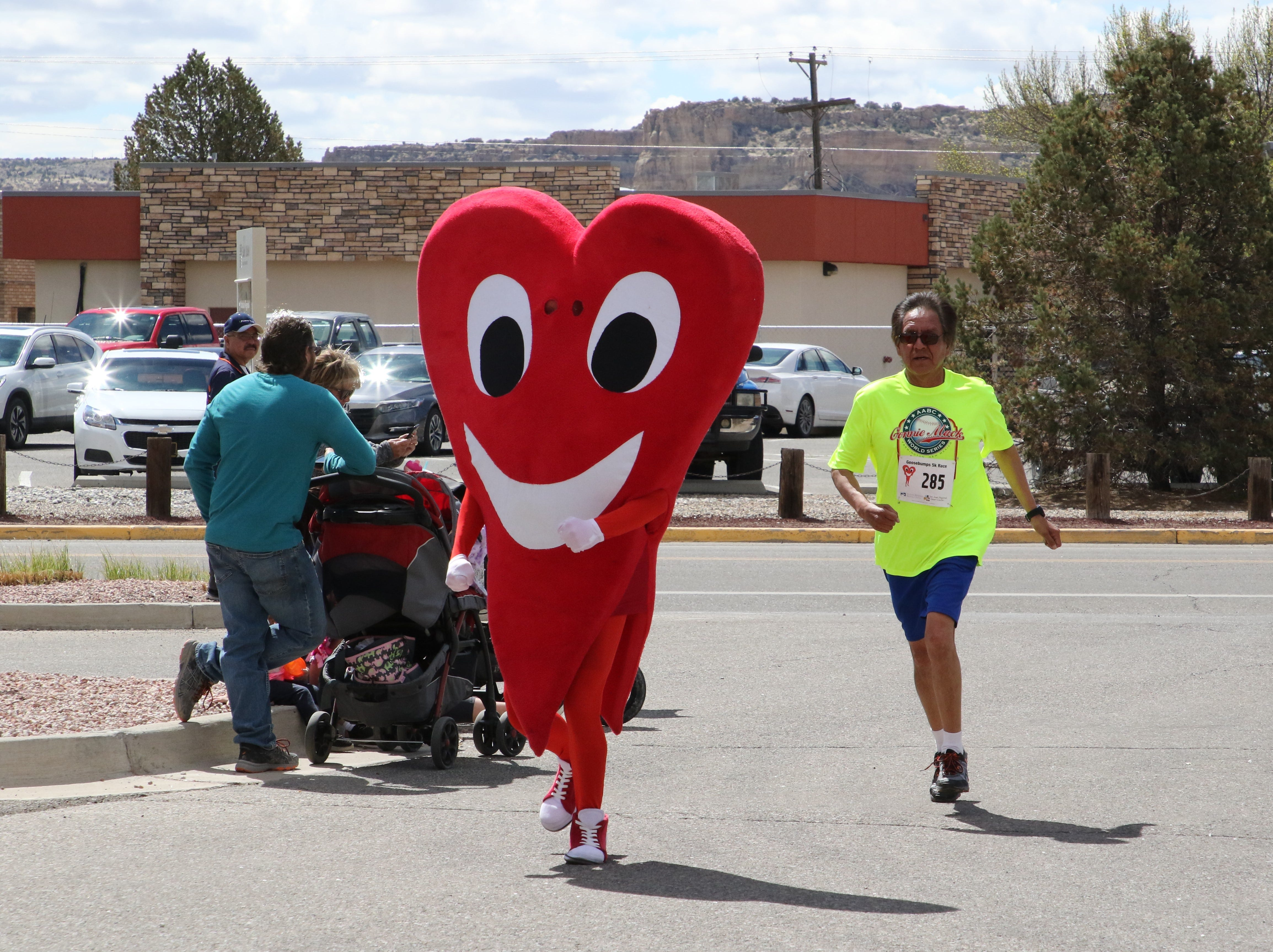 Mr. Juan Hart, the San Juan Regional Heart Center's mascot, runs with a participant on Saturday during the 11th annual A Fair of the Heart and Goosebump Race in Farmington.