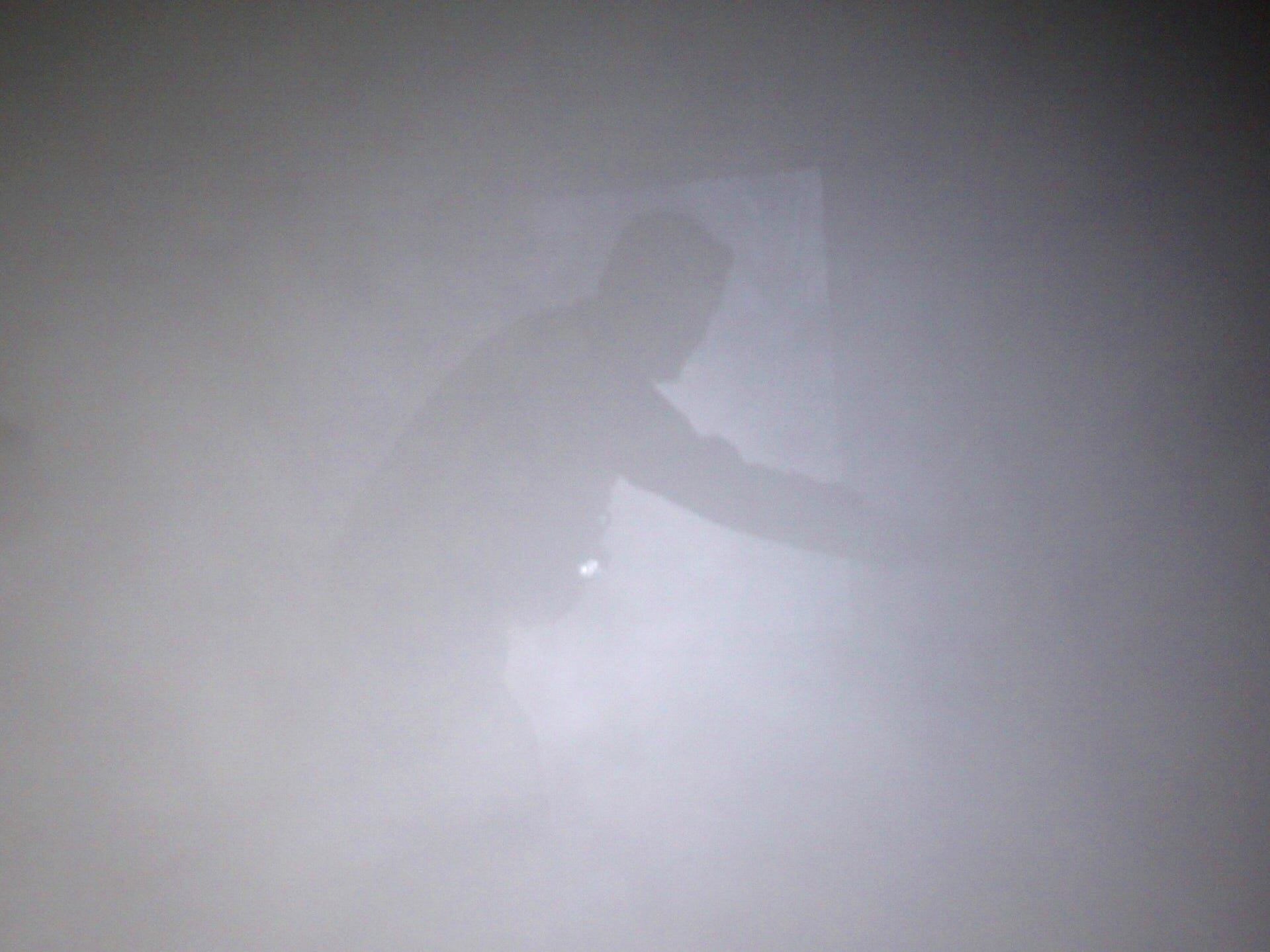 The outline of a firefighter, barely visible in the smoke of the Farmington Hills training house, looks to complete a mission while wearing full gear and a breathing apparatus.