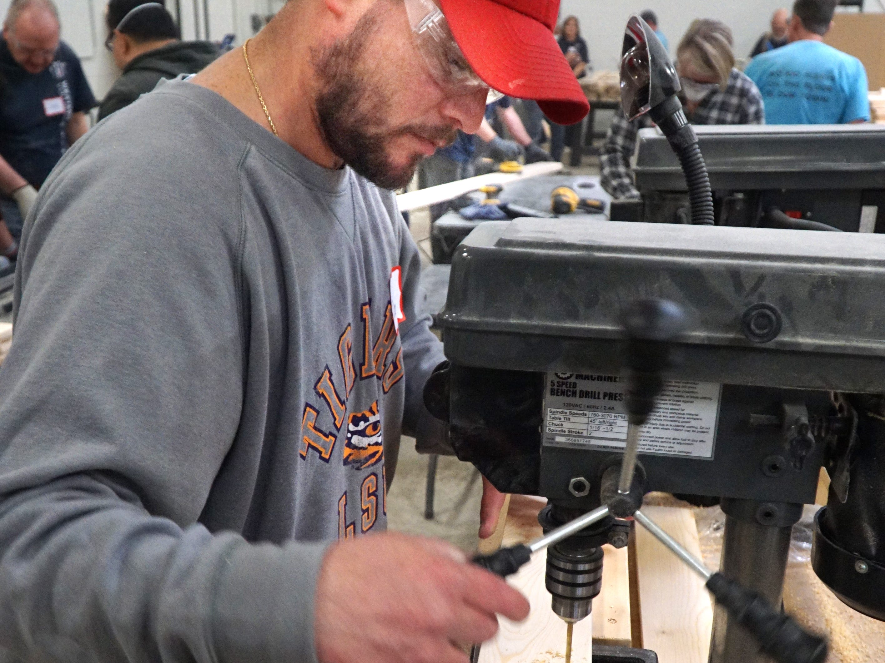 Derek Schraffenberger uses a drill press to make some precise holes in wood for the bunk bed building party in Livonia on April 13.