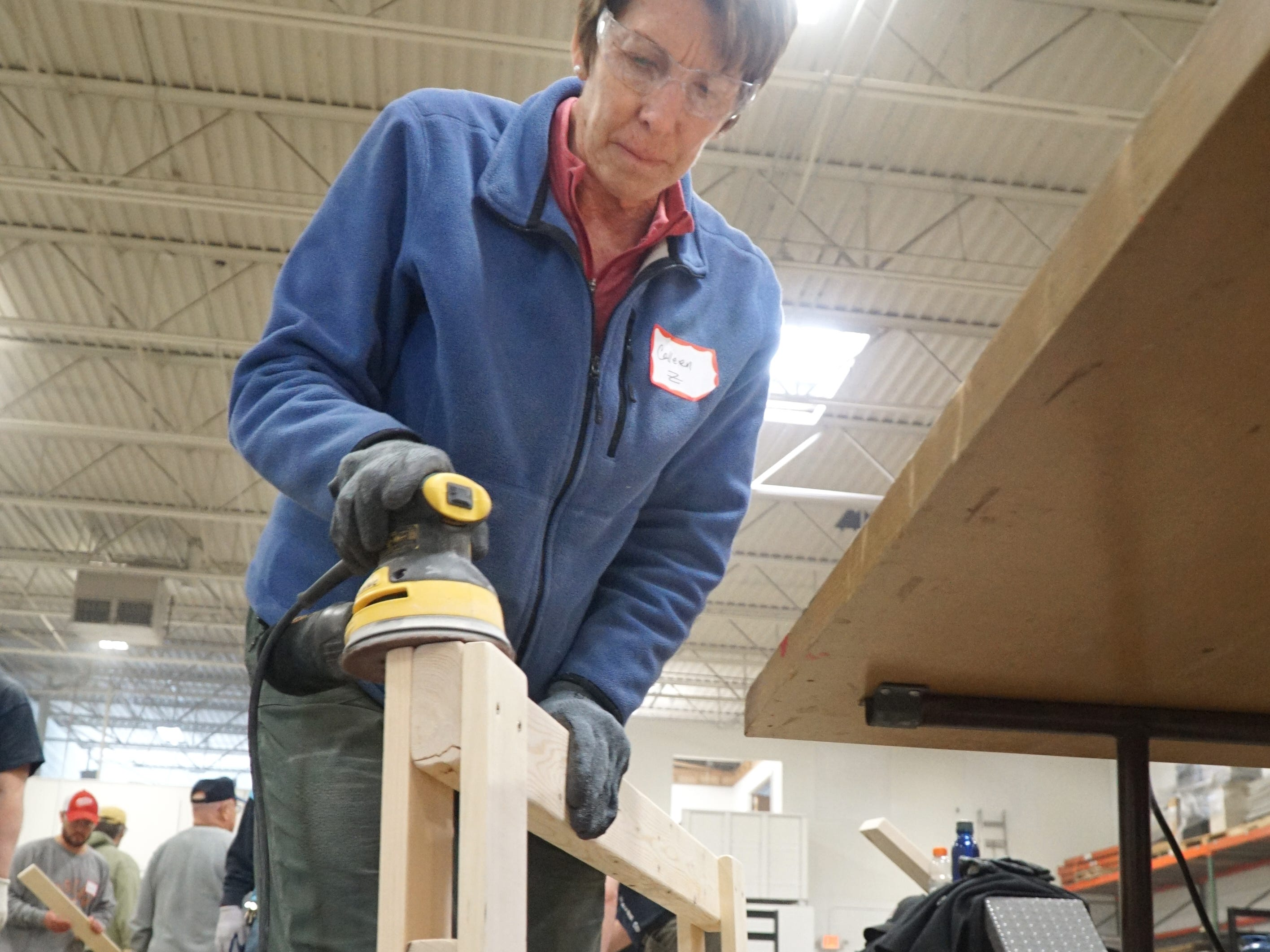 Colleen Zematic works on sanding part of a bunk bed during the April 13 volunteer effort in Livonia.