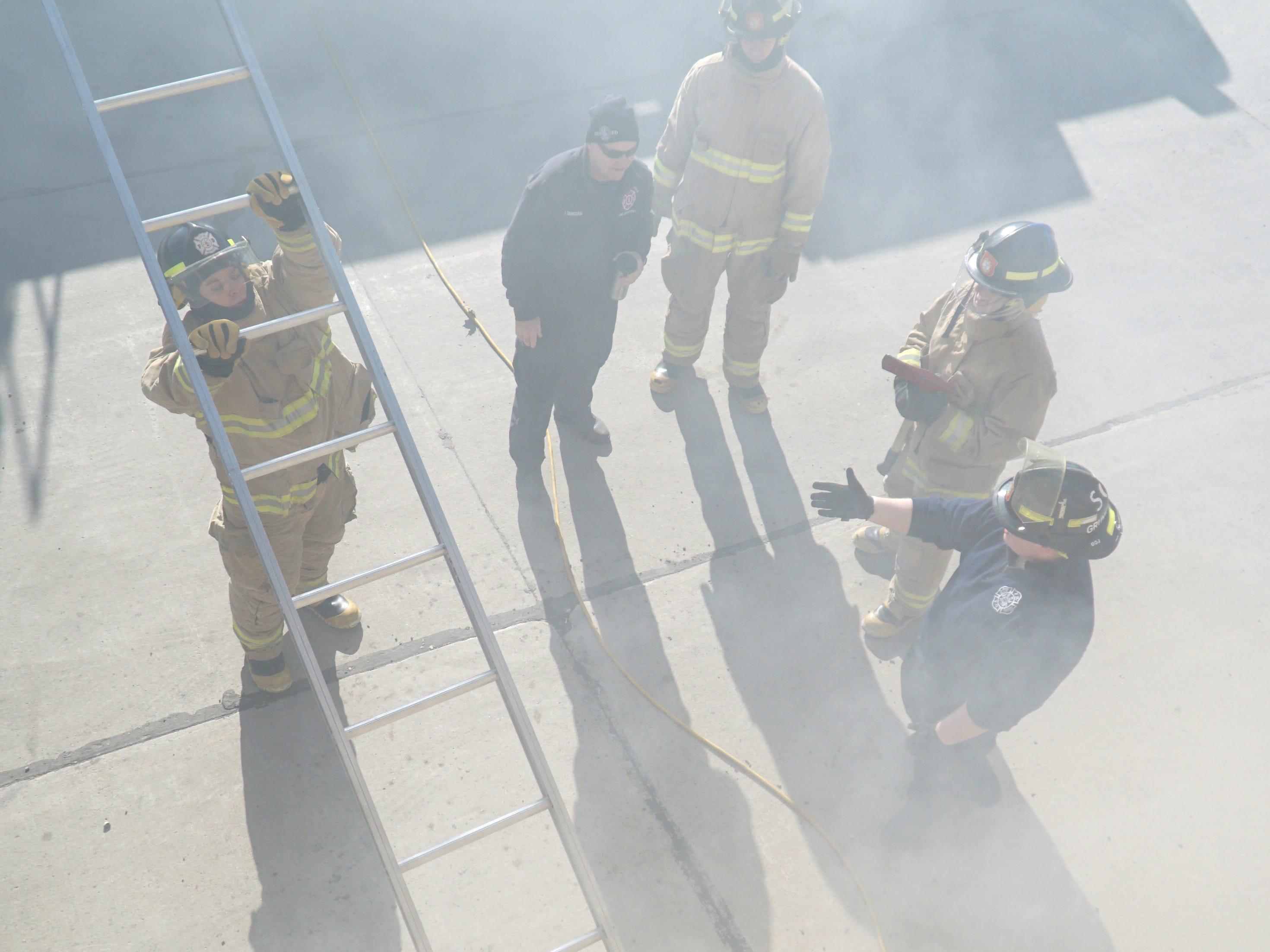 As seen from the upper level of the fire training house, recruits learn how to properly place and then climb ladders for fire fighting work.