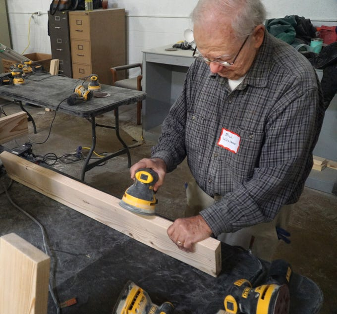 """Volunteer Bill Williams sands a two-by-four on April 13 at the Build and Bedding Drive at Joe's Trailers in Livonia. About 50 volunteers got together that day to build sets of bunk beds for needy families in the area so that, as their slogan goes: """"No Kid Sleeps on the Ground in Our Town"""". Funding for the bunk bed build came from West Bloomfield's Prince of Peace Church. The volunteers were set to build 20 bunk beds too."""