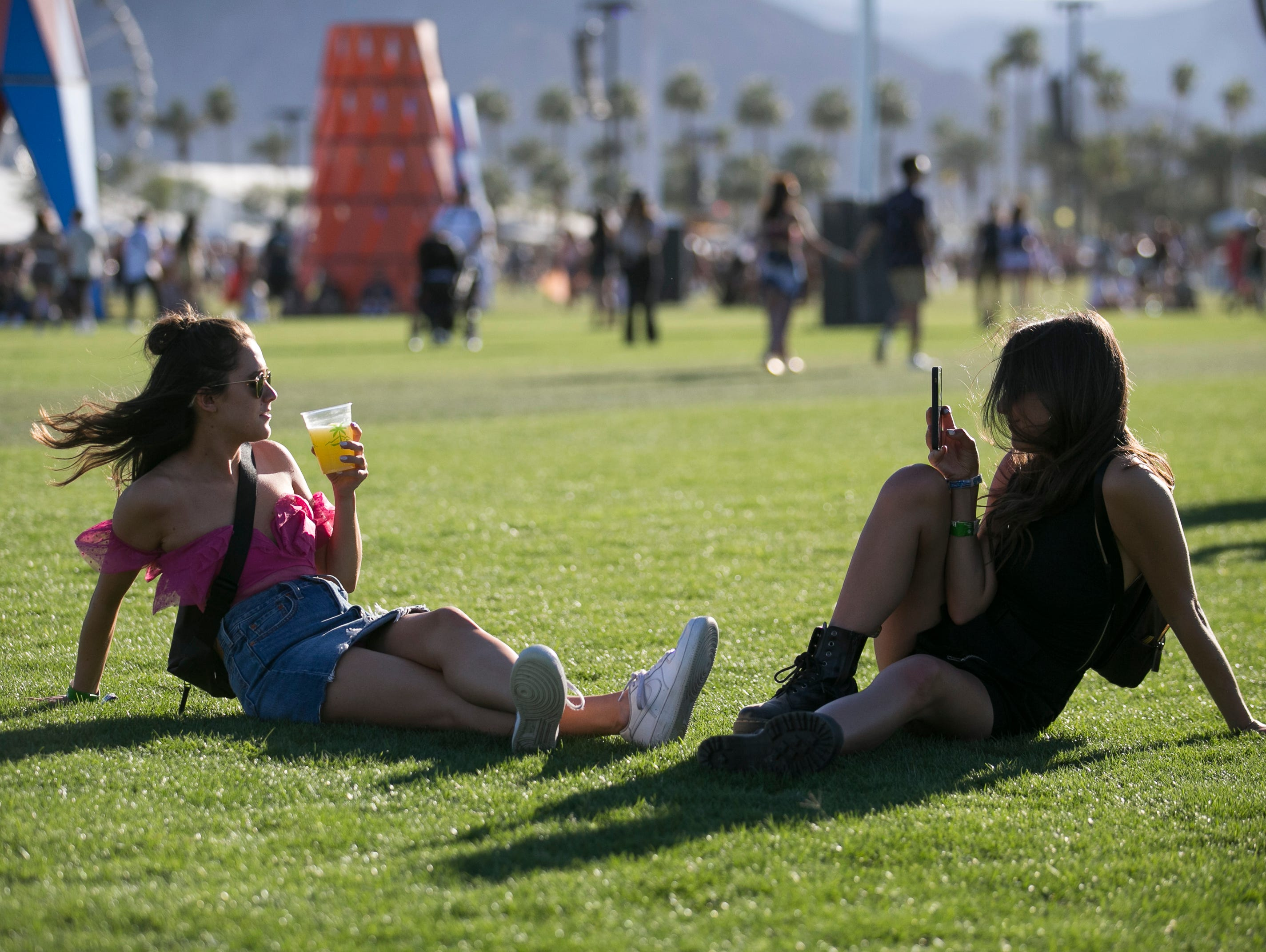 Savanna Stephens (left) and Ally Lucchesi (right) both from Los Angeles, sit in the grass at the Coachella Valley Music and Arts Festival in Indio, Calif. on Fri. April 12, 2019.