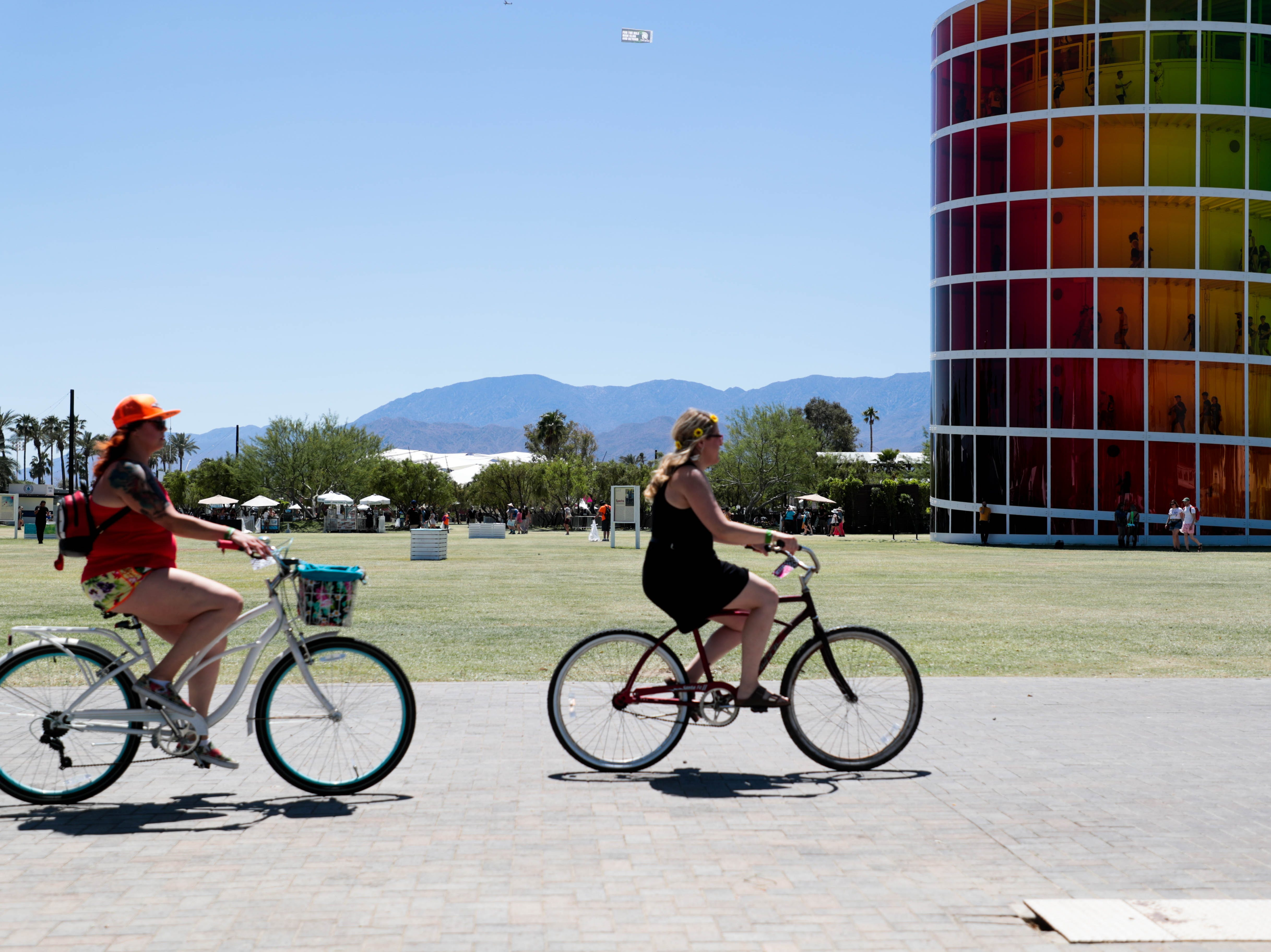 Two women ride bikes on Saturday, April 13, 2019 at Coachella Valley Music and Arts Festival in Indio, Calif.