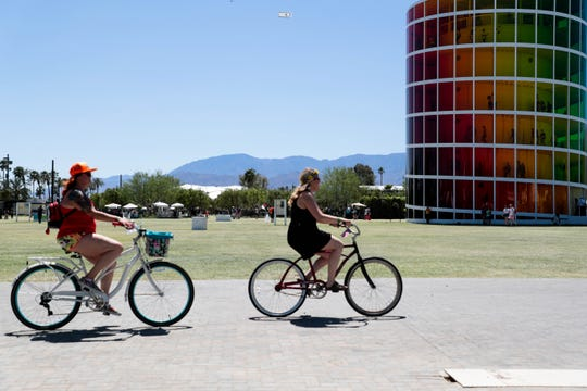 Two women ride bikes on Saturday, April 13, 2019, at Coachella Valley Music and Arts Festival in Indio, Calif.