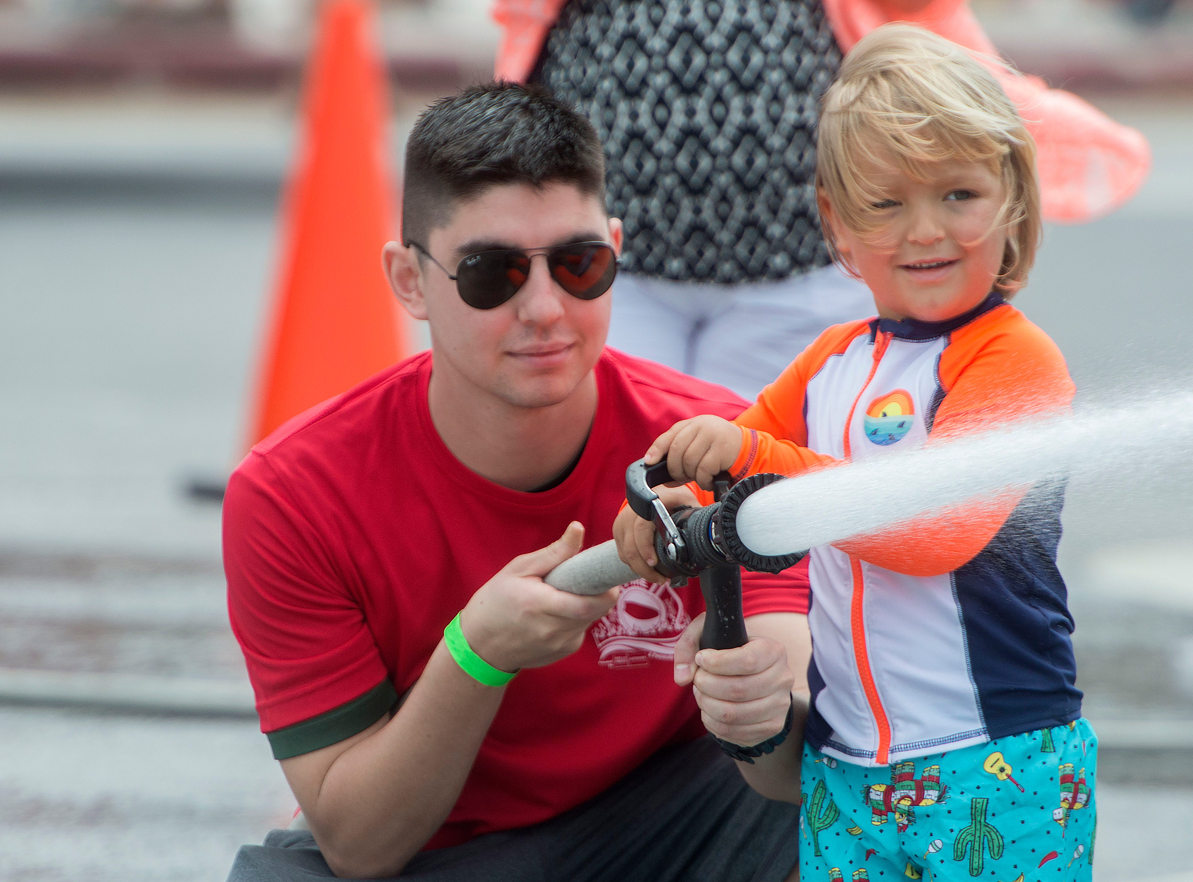 Kids play firefighters during the fifth annual Pensacola Beach Firefighters Challenge. The event tested the strength, agility, teamwork, and skills of firefighters as well as provided a fun, family friendly event for participants and the public.