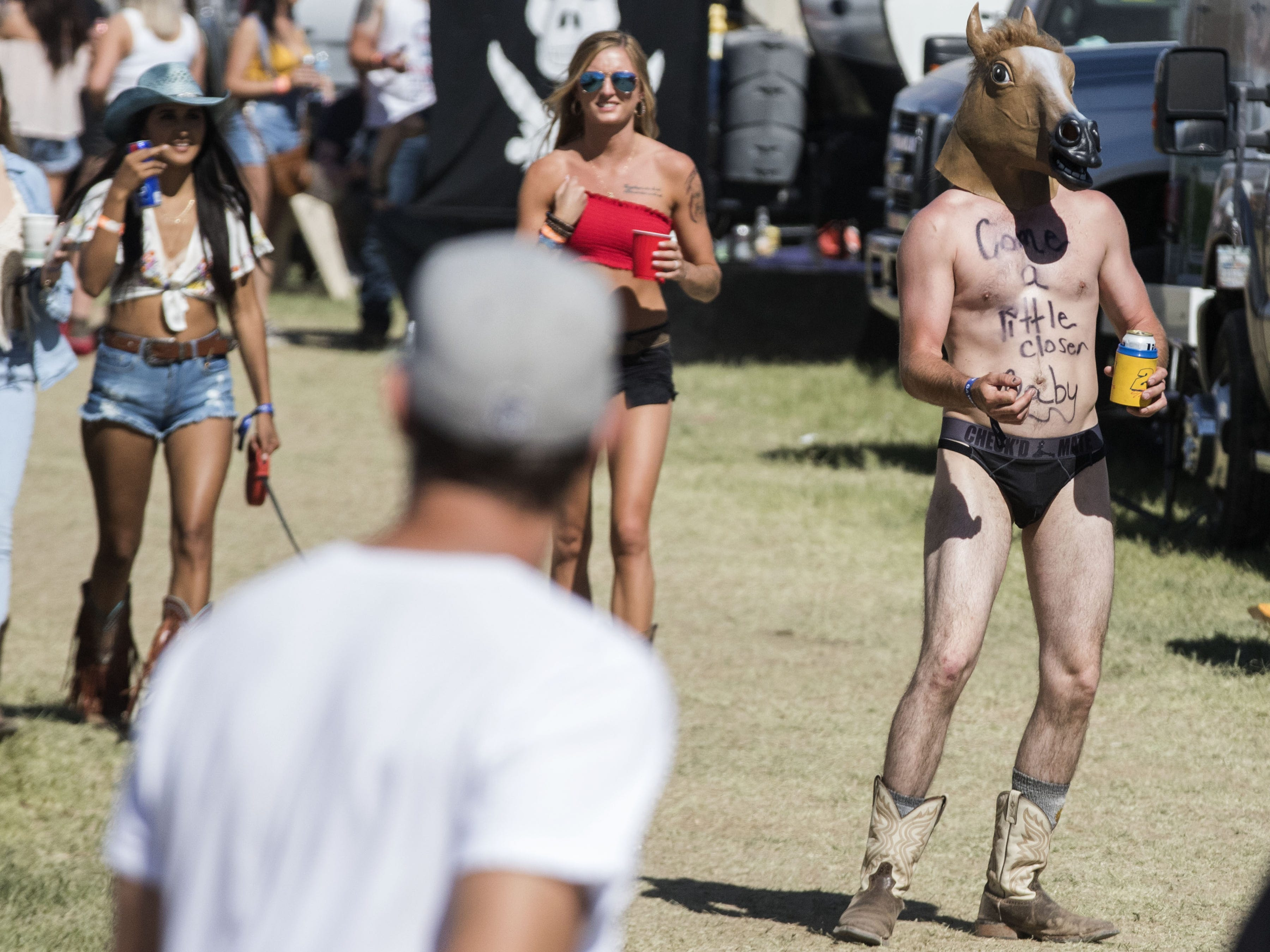 Festival-goers watch a man in a horse's head walk by during Country Thunder Arizona Saturday, April 13, 2019, in Florence, Ariz.