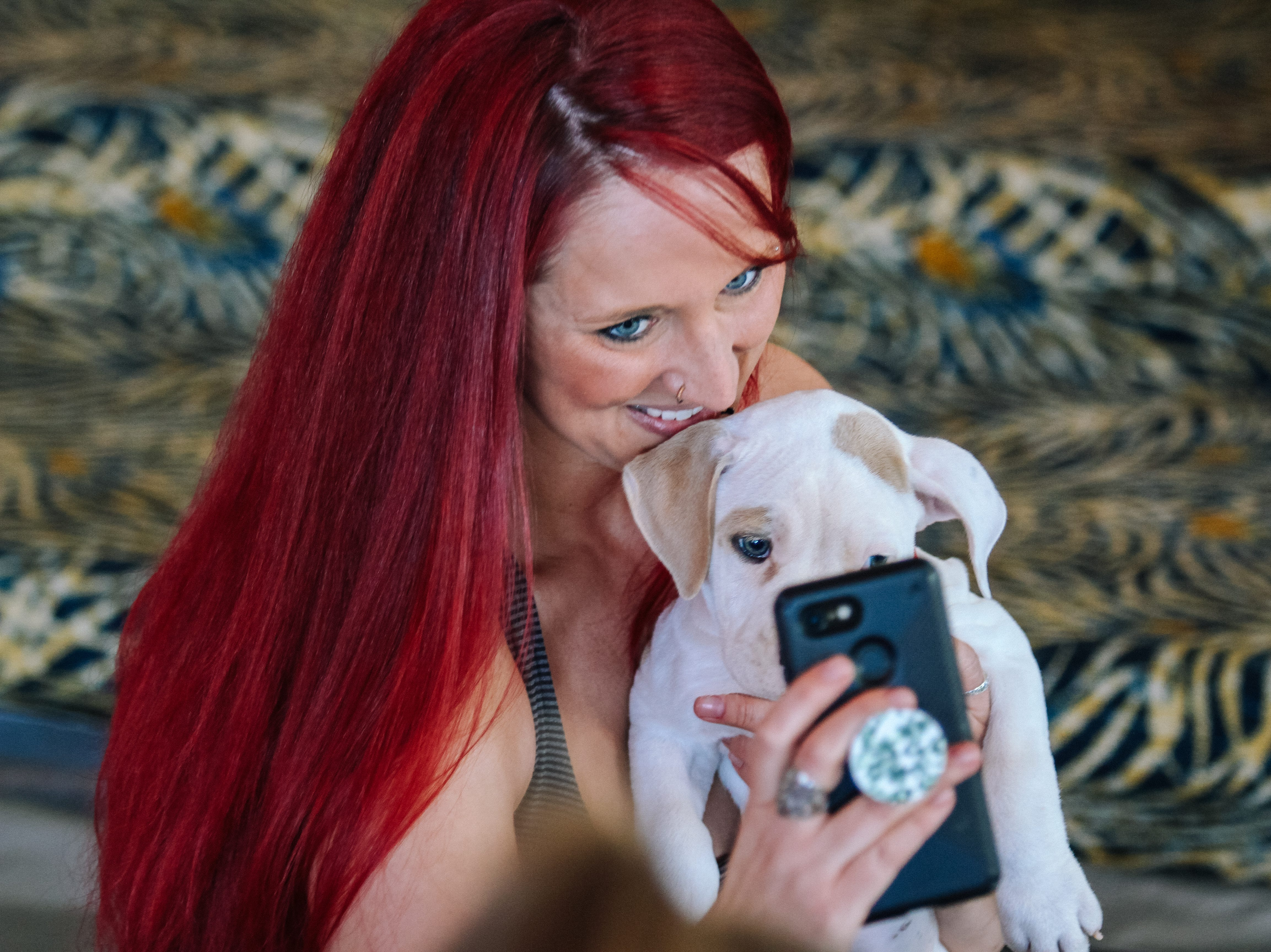 Attendees play with puppies at Puppies, Pilates and Prosecco, an event hosted by Almost There Foster Care at the Wrigley Mansion in Phoenix on April 13, 2019.