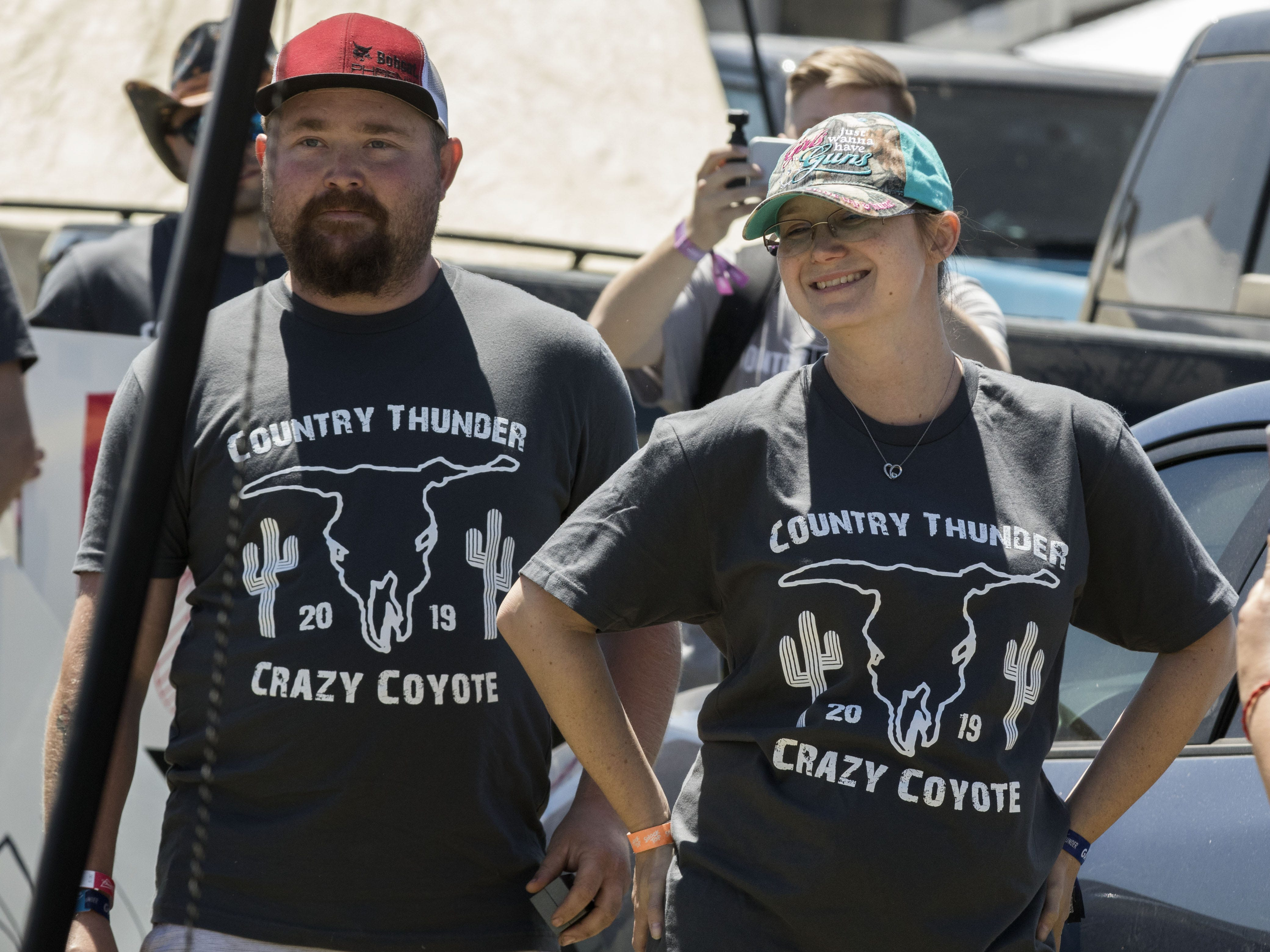 """Tahnee Billingsly (center) reacts as she sees signs asking """"Will You Marry Me"""" as her husband to be Justin Adams (left) surprises her with a proposal surrounded by family and friends during Country Thunder Arizona Saturday, April 13, 2019, in Florence, Ariz."""