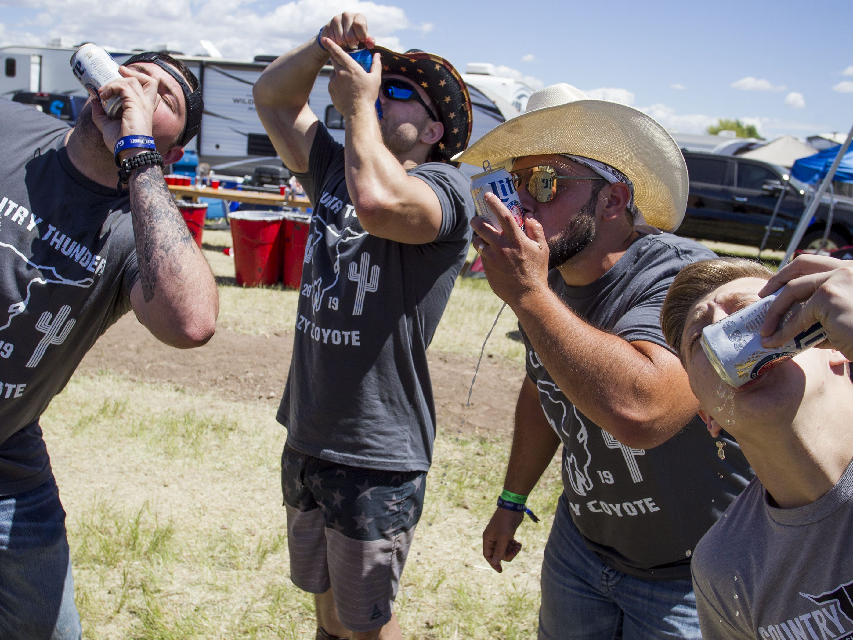Guys shotgun beers during Country Thunder Arizona Saturday, April 13, 2019, in Florence, Ariz.