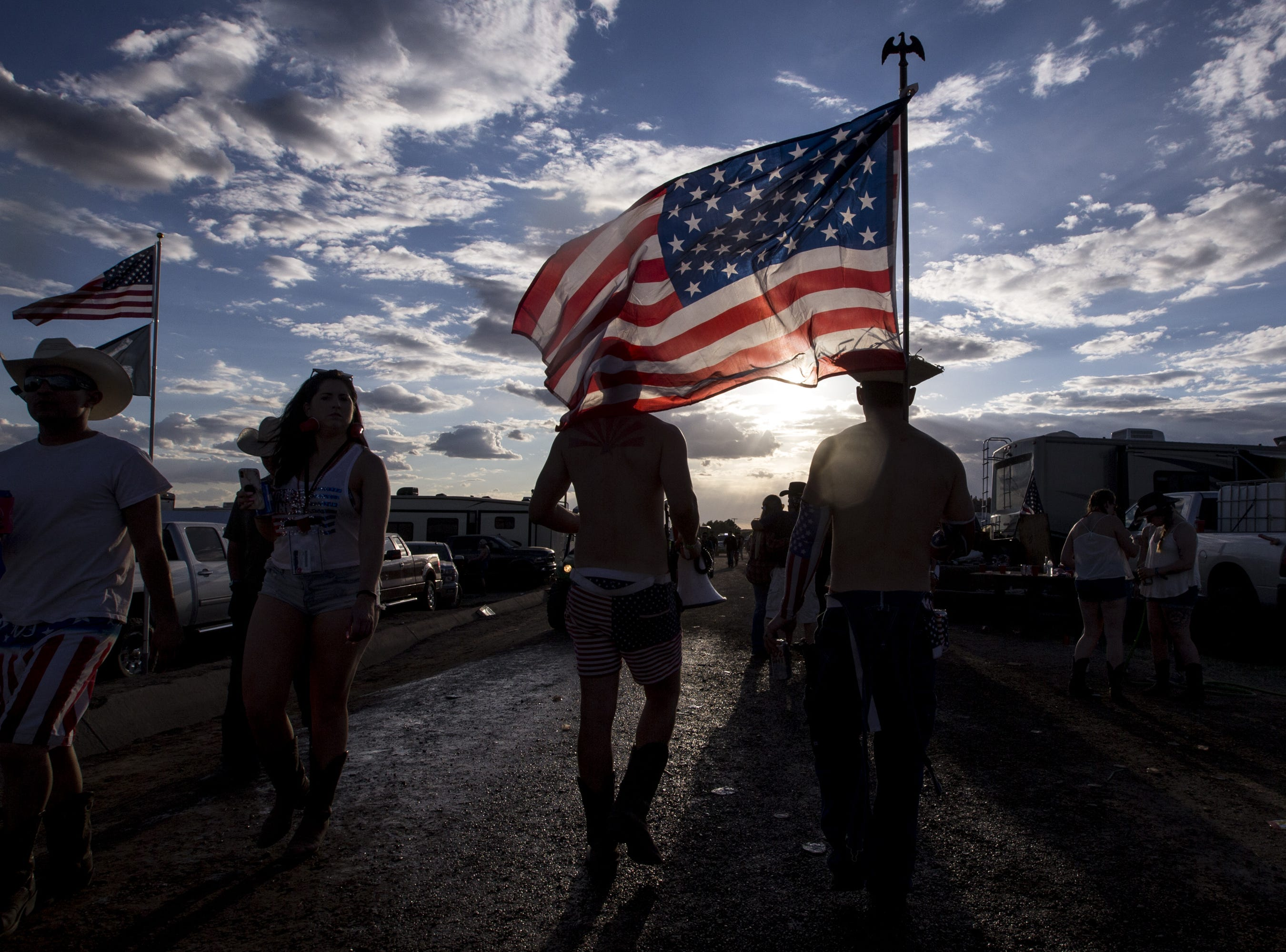 Josh Fowler carries an American flag at the Crazy Coyote campground on Friday, April 12, 2019, during Day 2 of Country Thunder Arizona in Florence, Ariz.