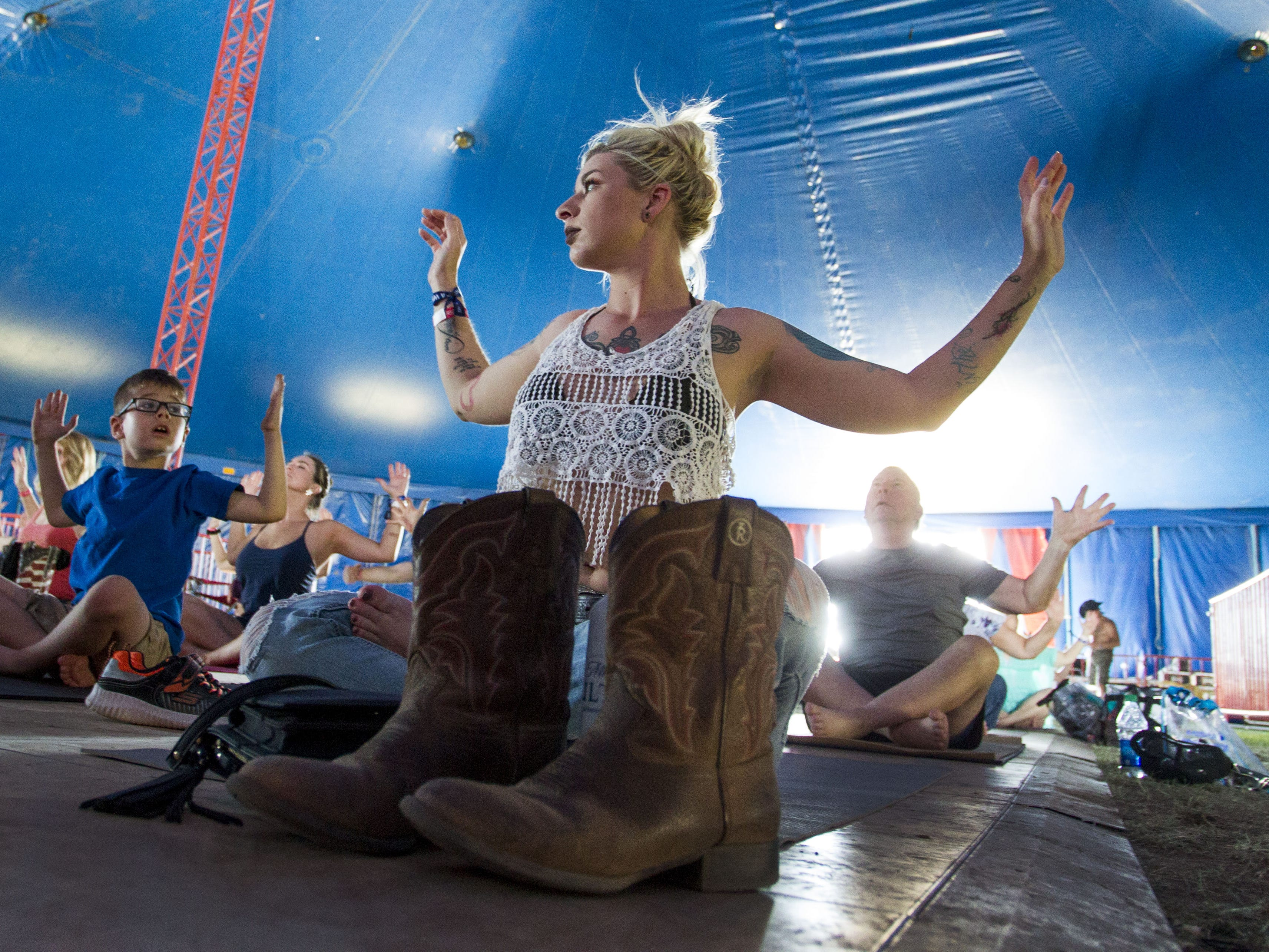 Sarah Owens of Florence stretches with her son Tyler, 6, during a yoga session at Country Thunder Arizona Saturday, April 13, 2019, in Florence, Ariz.