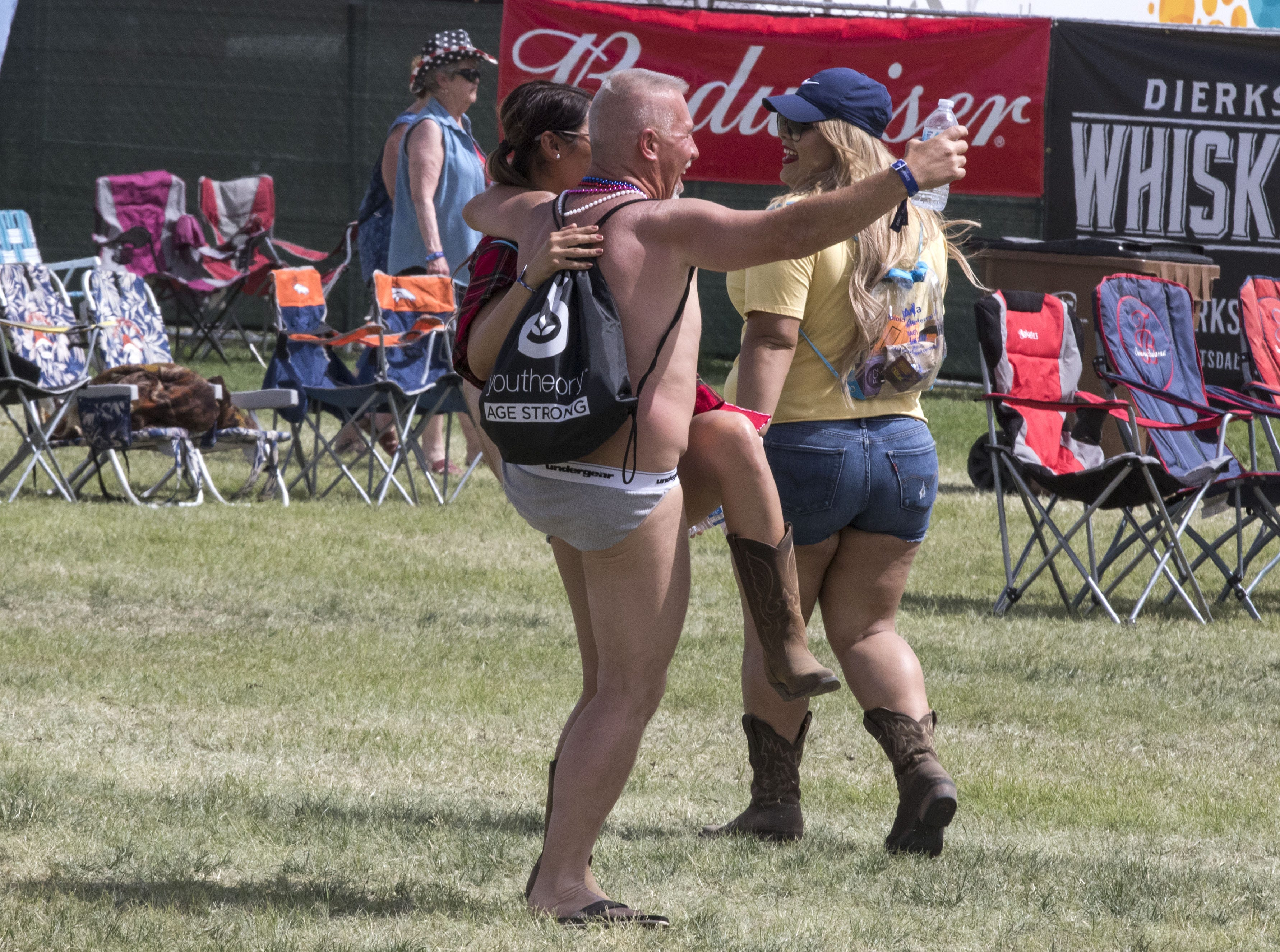 Donning only bikini briefs, flip flops and a backpack John Schmidt of Mesa parties it up with fans during Country Thunder Arizona Friday, April 12, 2019, in Florence, Arizona.