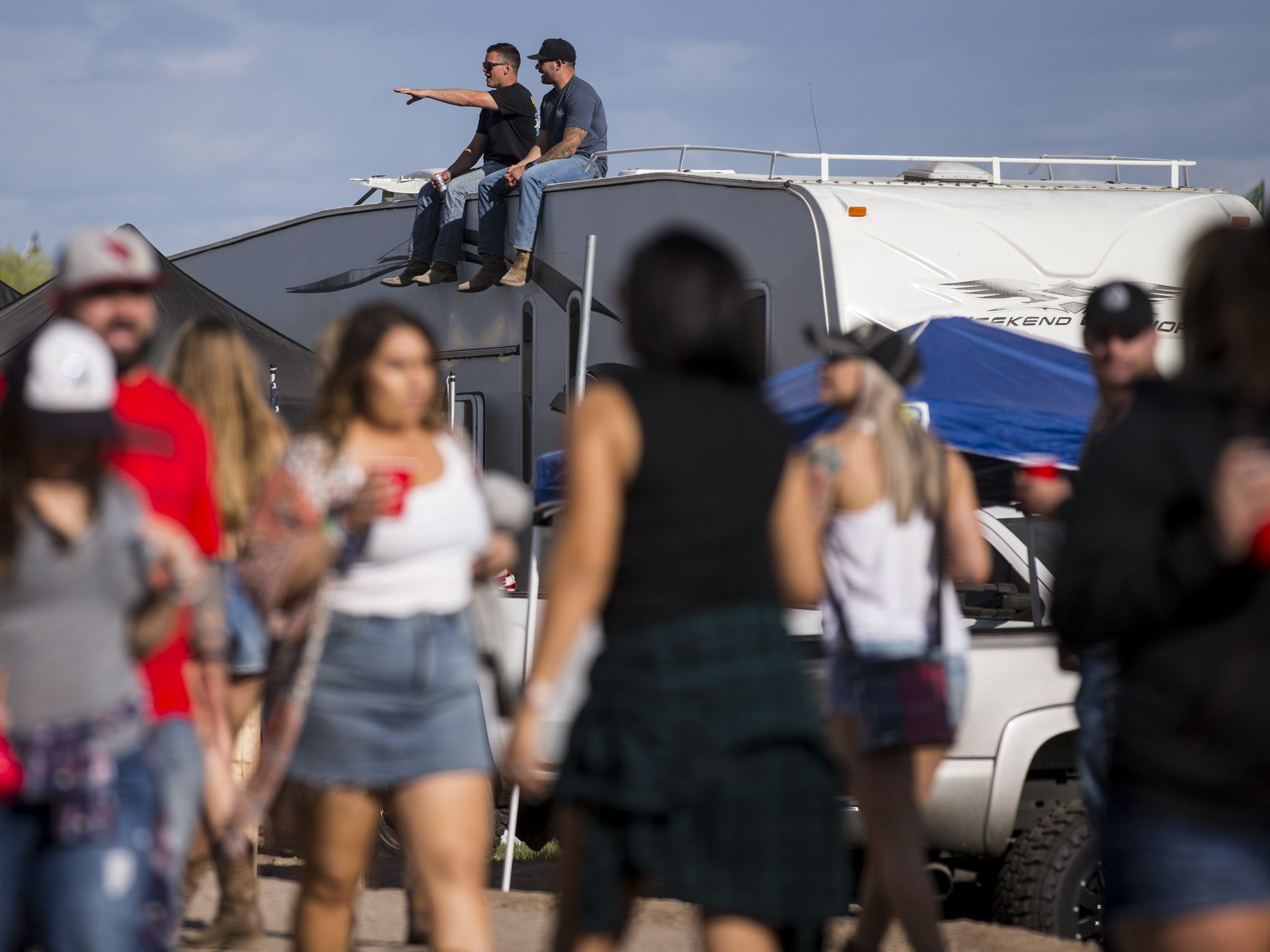 People sit on top of an RV on Friday, April 12, 2019, during Day 2 of Country Thunder Arizona in Florence, Ariz.