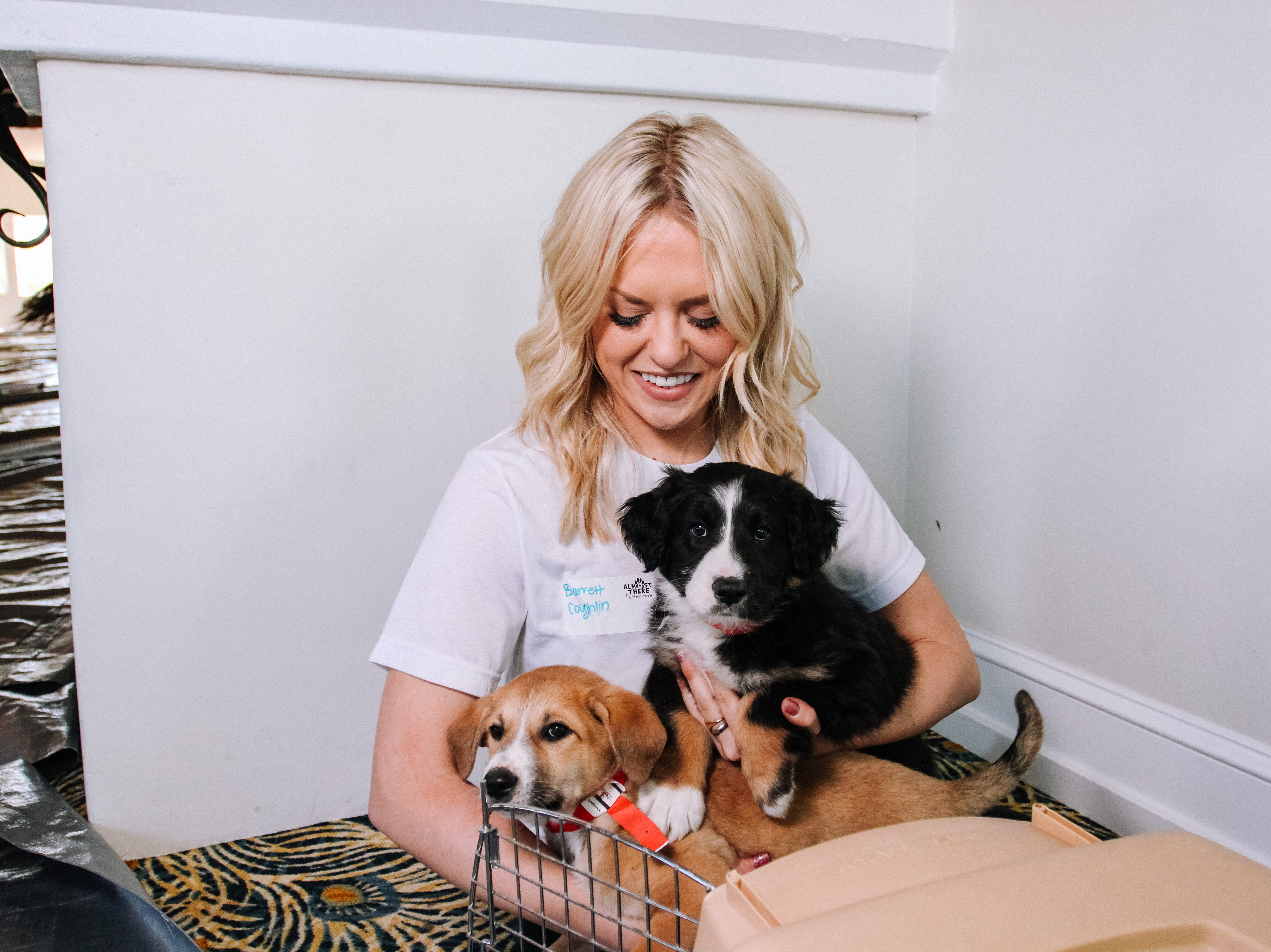 Barrett Couhlin, a volunteer with Almost There Foster Care, puts puppies in their kennel at Puppies, Pilates and Prosecco, an event hosted by Almost There Foster Care at the Wrigley Mansion in Phoenix on April 13, 2019.