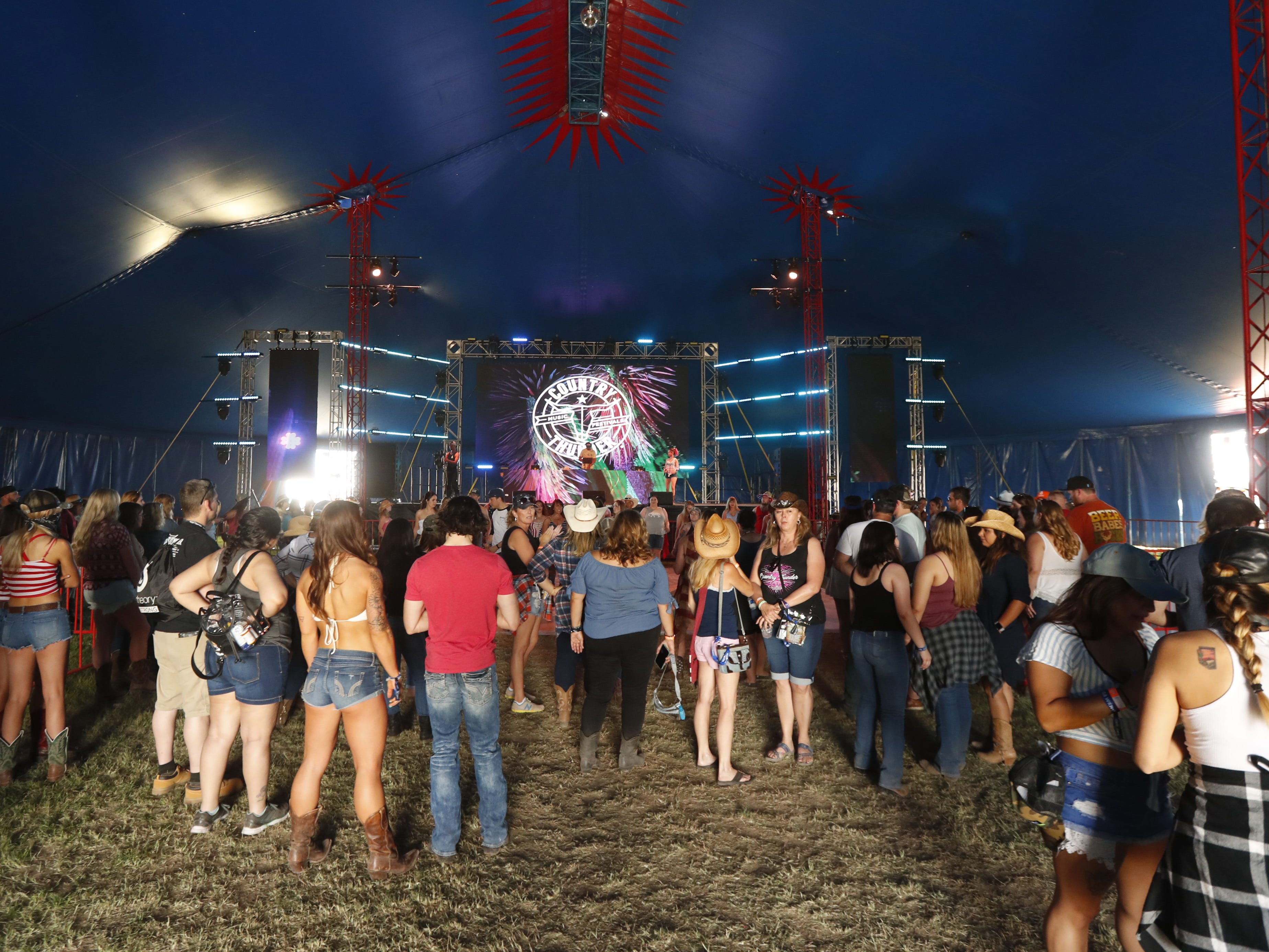Country music fans watch as others dance at Electric Thunder tent during Country Thunder in Florence, Ariz., on Friday, April 12, 2019.