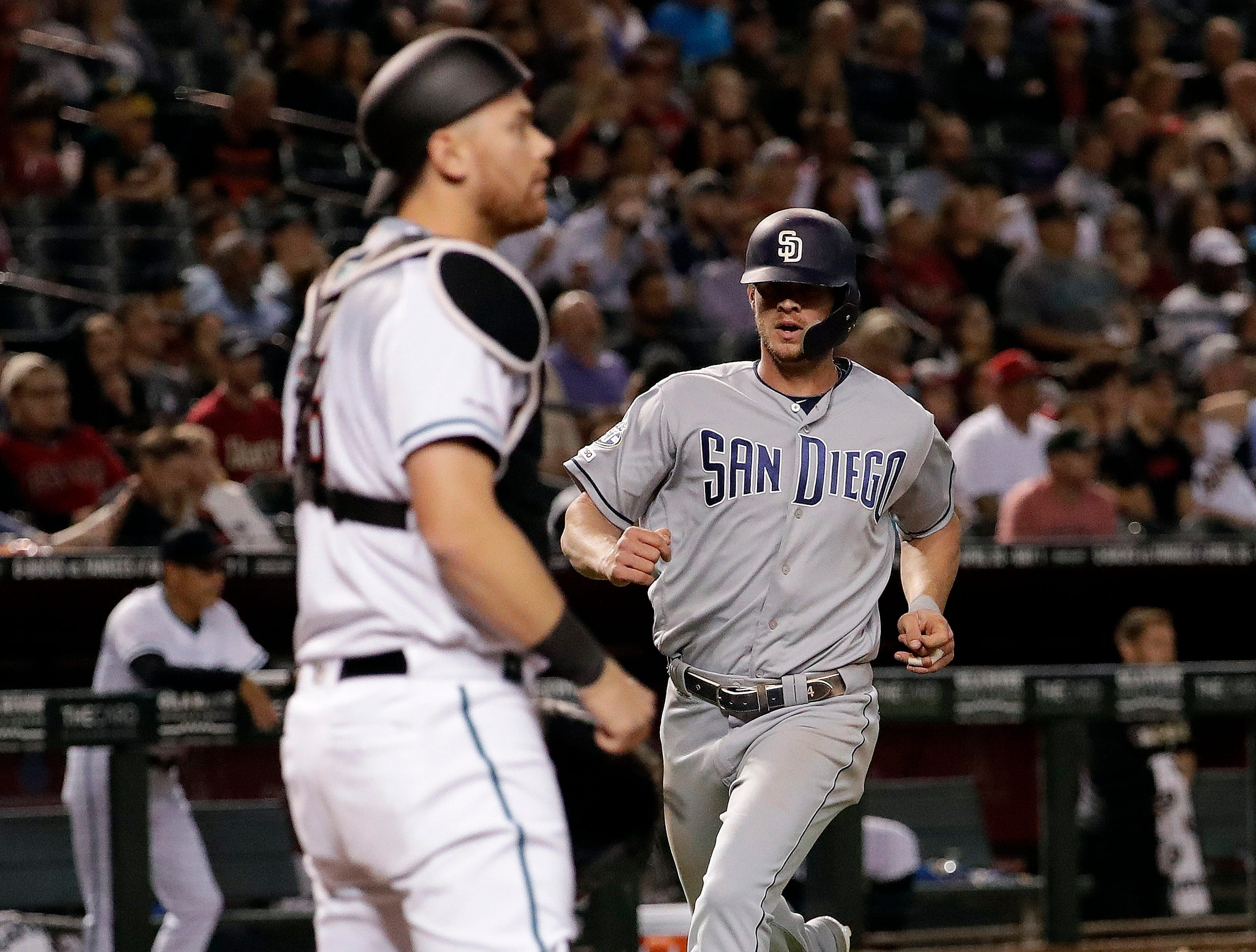 San Diego Padres Wil Myers scores on a double hit by Fernando Tatis Jr. during the seventh inning of a baseball game as Arizona Diamondbacks catcher Carson Kelly waits for the throw, Friday, April 12, 2019, in Phoenix. (AP Photo/Matt York)