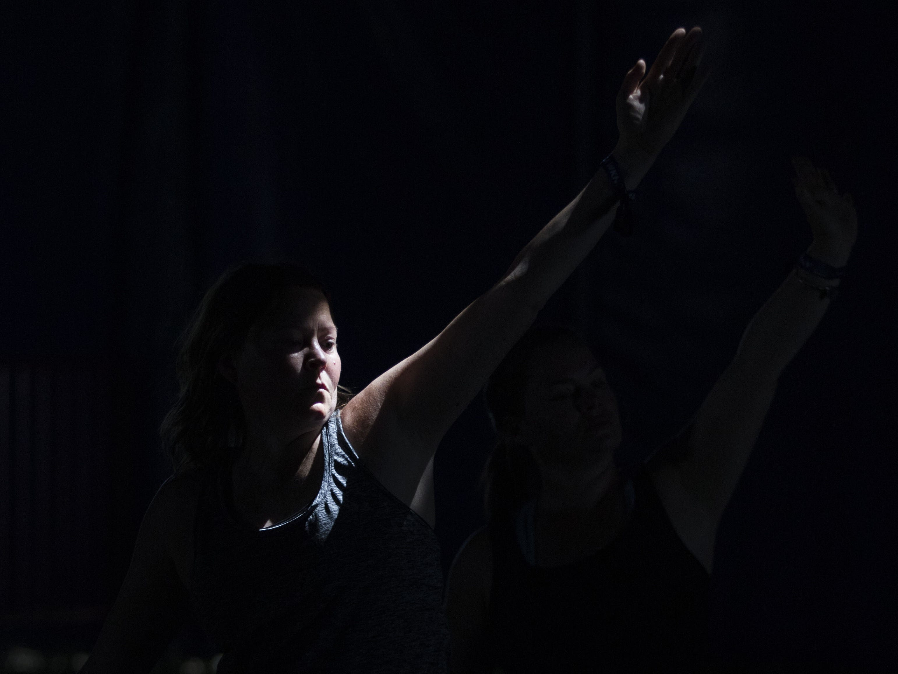 Sunlight streams in through a hole in the tent as a yoga student practices her craft during Country Thunder Arizona Saturday, April 13, 2019, in Florence, Ariz.