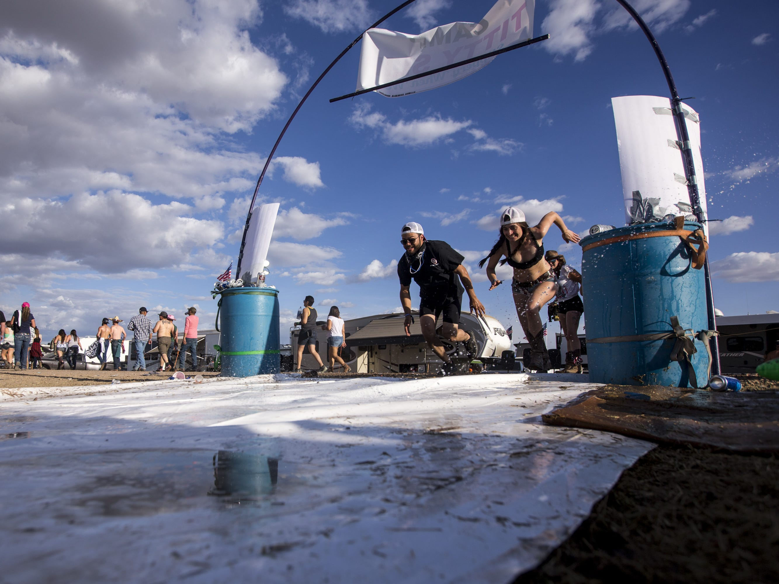 Nic McKee and Brooke Humphrey run to a slip and slide at the Crazy Coyote campground on Friday, April 12, 2019, during Day 2 of Country Thunder Arizona in Florence, Ariz.
